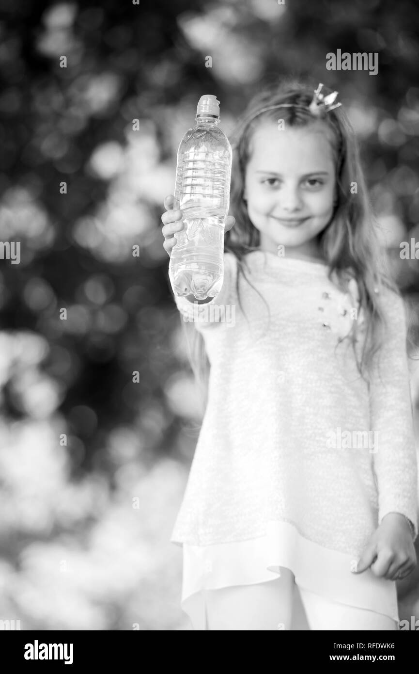 Water bottle in hand of small child on blurred natural background. Girl princess hold fresh water. Thirst and dehydration. Refreshment and freshness. Childhood and childcare, black and white. - Stock Image