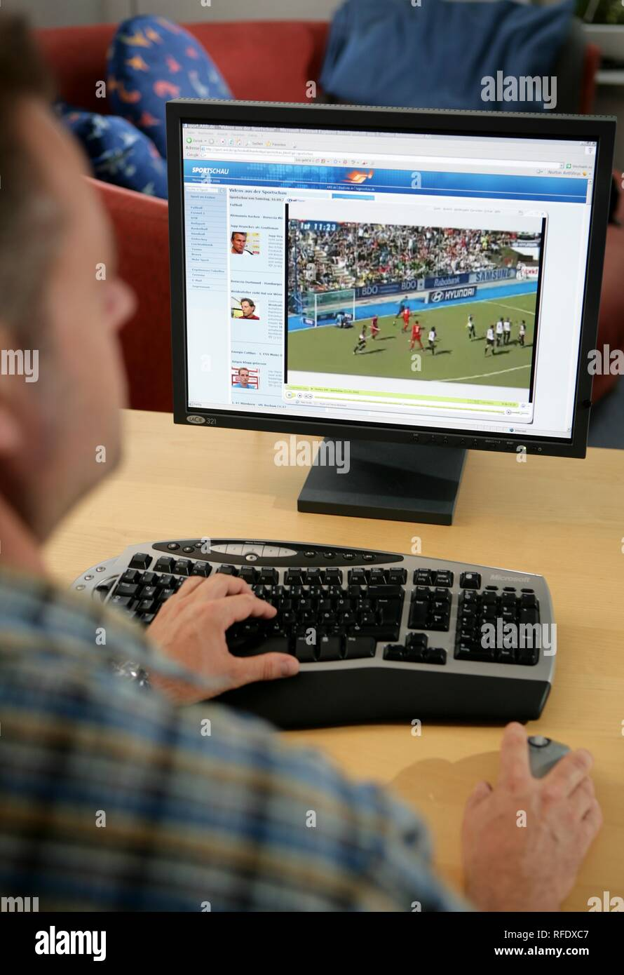 DEU, Germany : Man is sitting at a computer, surfing the internet. German TV ARD, livestream TV, sport news. | - Stock Image