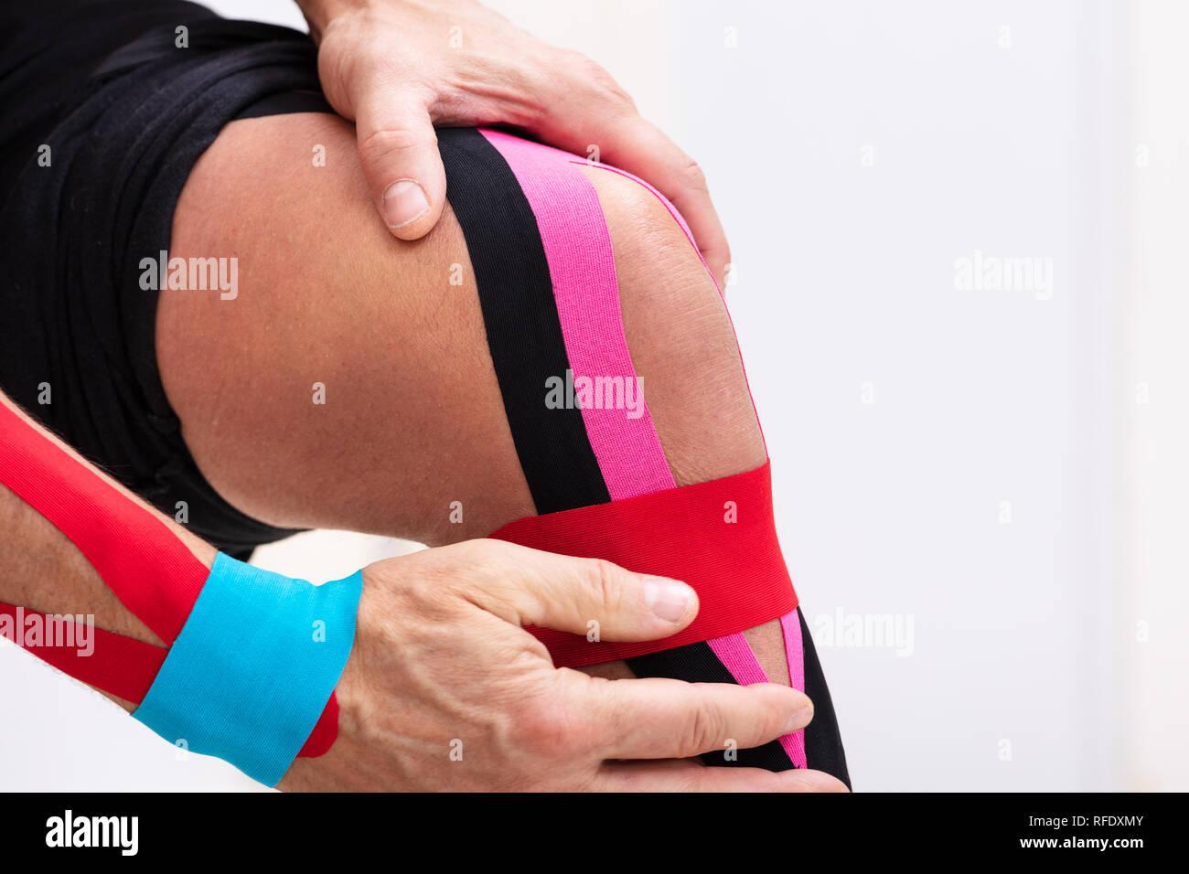 Man Sitting On Table Applying Kinesiology Tape On His Knee - Stock Image