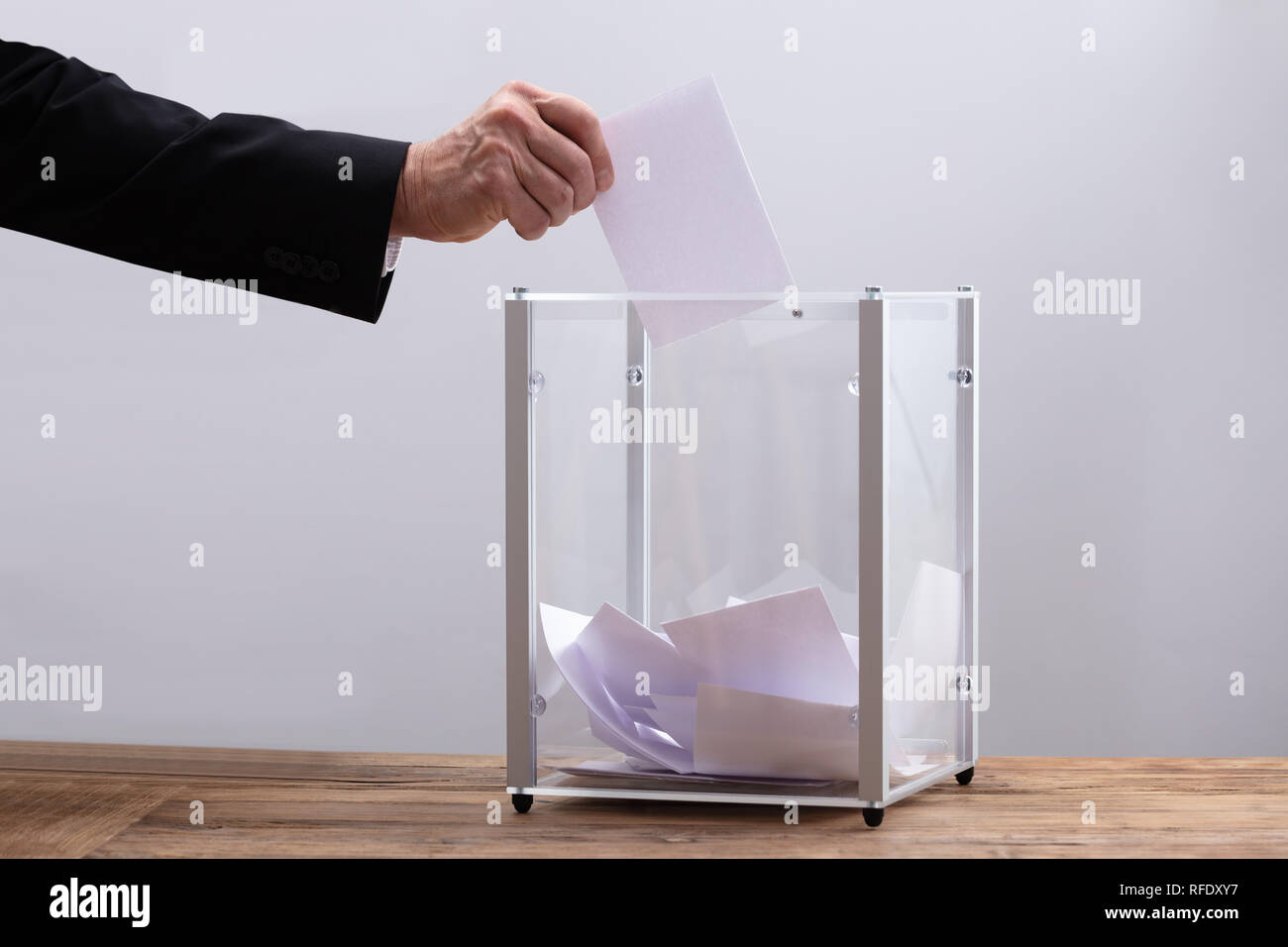 Close-up Of Businessman's Hand Inserting Ballot In A Glass Box - Stock Image