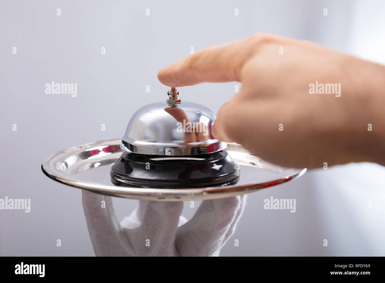 Close-up Of Person's Hand Ringing Service Bell On Plate Held By Waiter - Stock Image