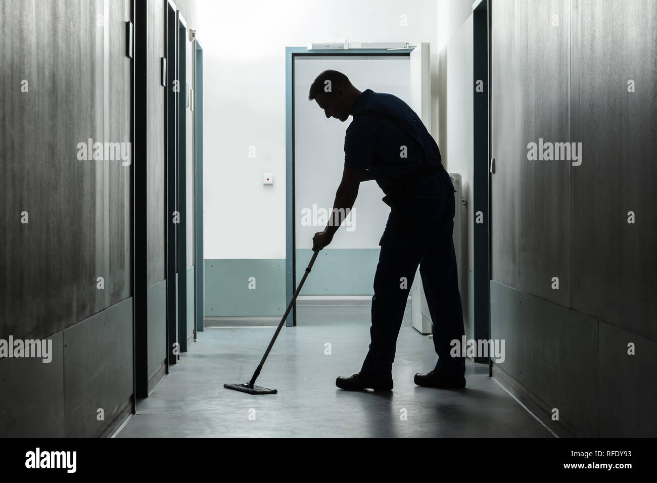 Side View Of Man Cleaning Floor With Mop - Stock Image