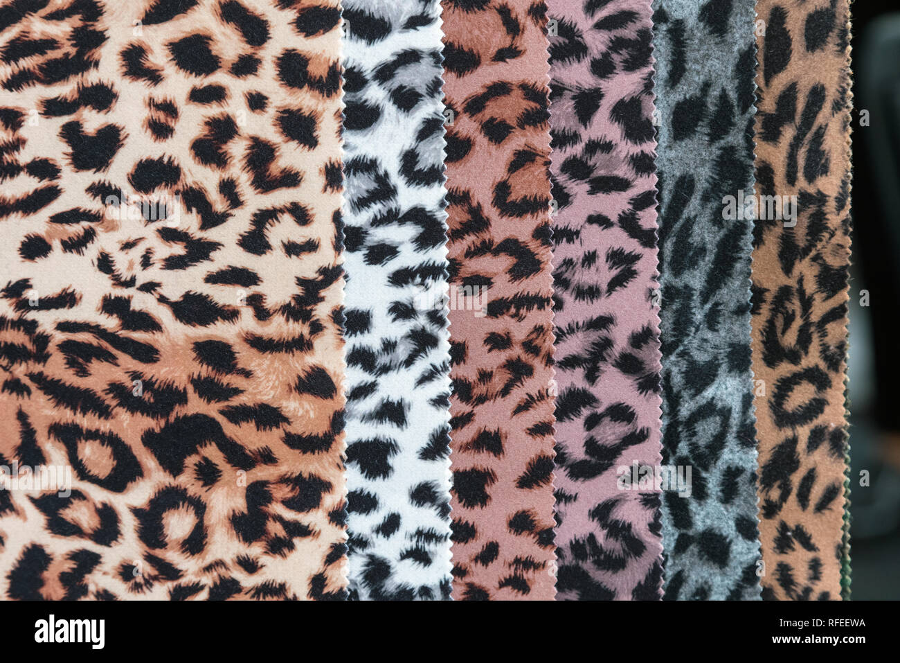 Fabric and textiles samples in a factory shop or store that mimic animal skin. Different colors and patterns on the market. Industrial fabrics. - Stock Image