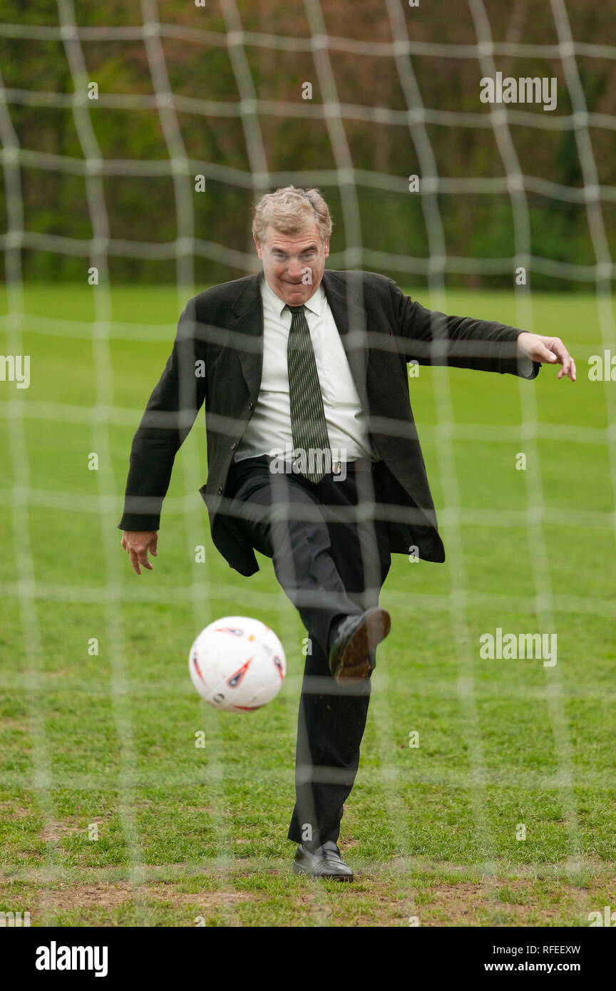 Former England footballer Trevor Brooking  international West Ham MBE kicking a football towards a net like taking  penalty kick. - Stock Image