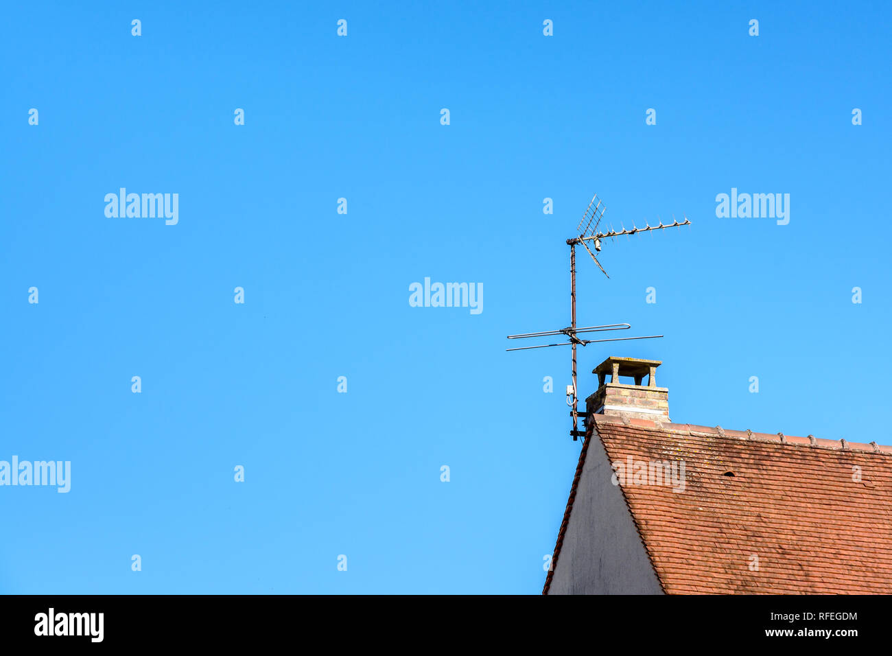 Low angle view of a TV antenna fixed to the chimney on the tile roof of a detached house against blue sky. - Stock Image