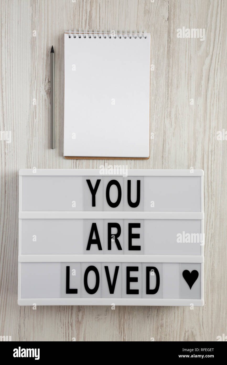 Modern board with text 'You are loved', notepad and pencil