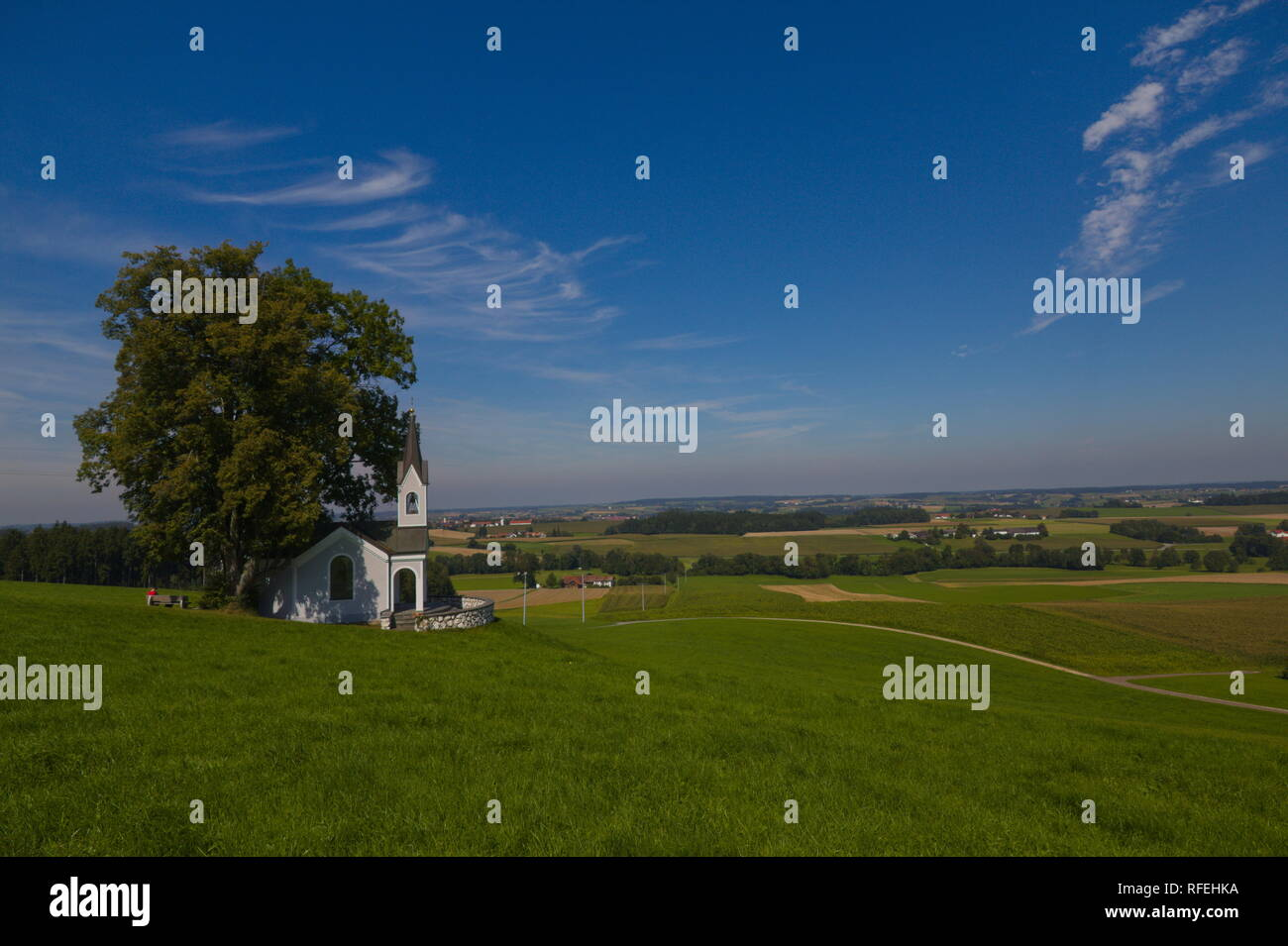 Scenic view over the Isental in Bavaria with a chapell and a cloudy blue sky - Stock Image