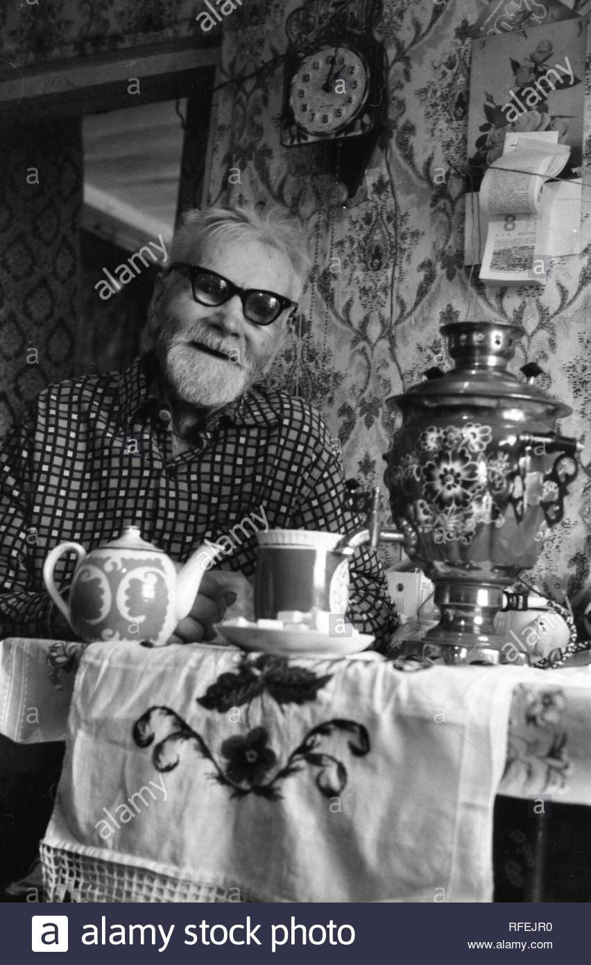 Bearded owner of the house is sitting at the table. Samovar with the tea is on the table. He is 100 years old! He was very hospitable! I took this photo, when I was travelling across villages in Smolensk region. I needed to know the way and than I saw old man on the street. He invited me to his house and treated very hearty. We drunk tea, speaking about life. His surname is Ivanov. Unfortunately, I dont remember his name... - Stock Image