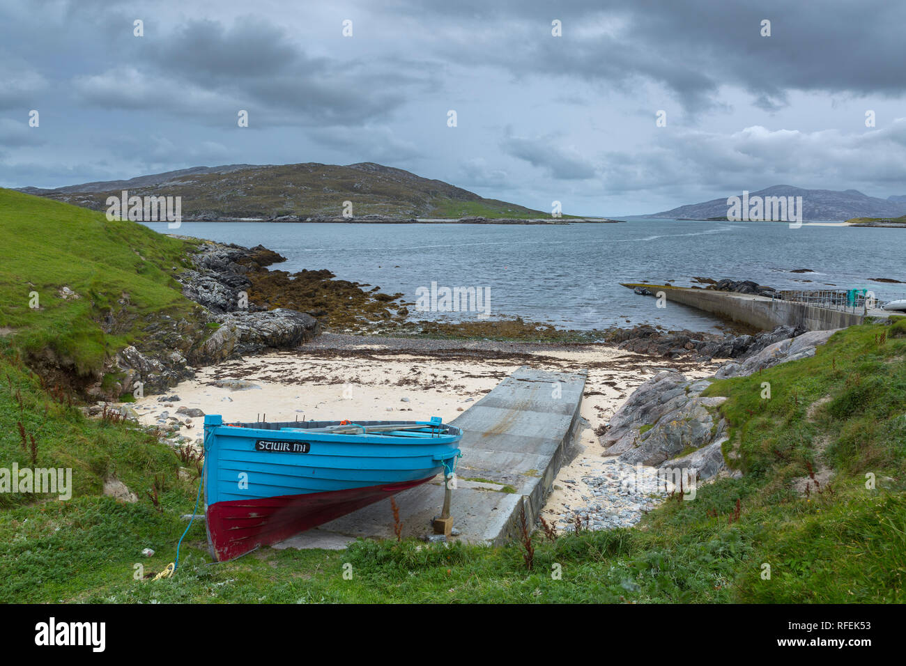 Blue and red boat at the jetty near Huisinis, Isle of Harris, Scotland. Looking across the water towards Scarp. - Stock Image