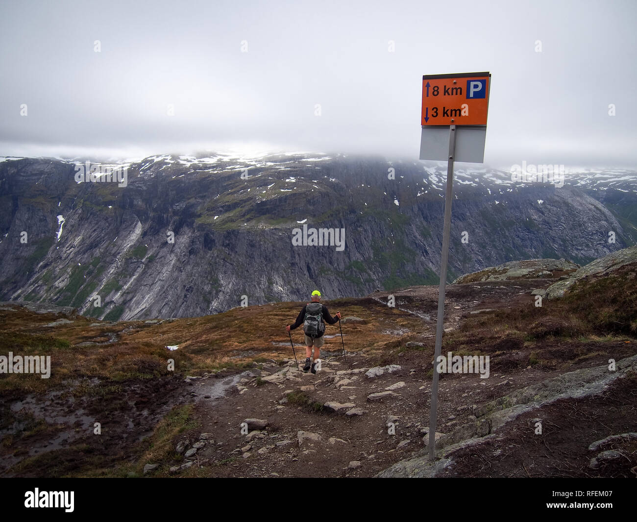 Road sign on the mountain way to the Trolltunga, Norway and nordic walking man tourist near it - Stock Image