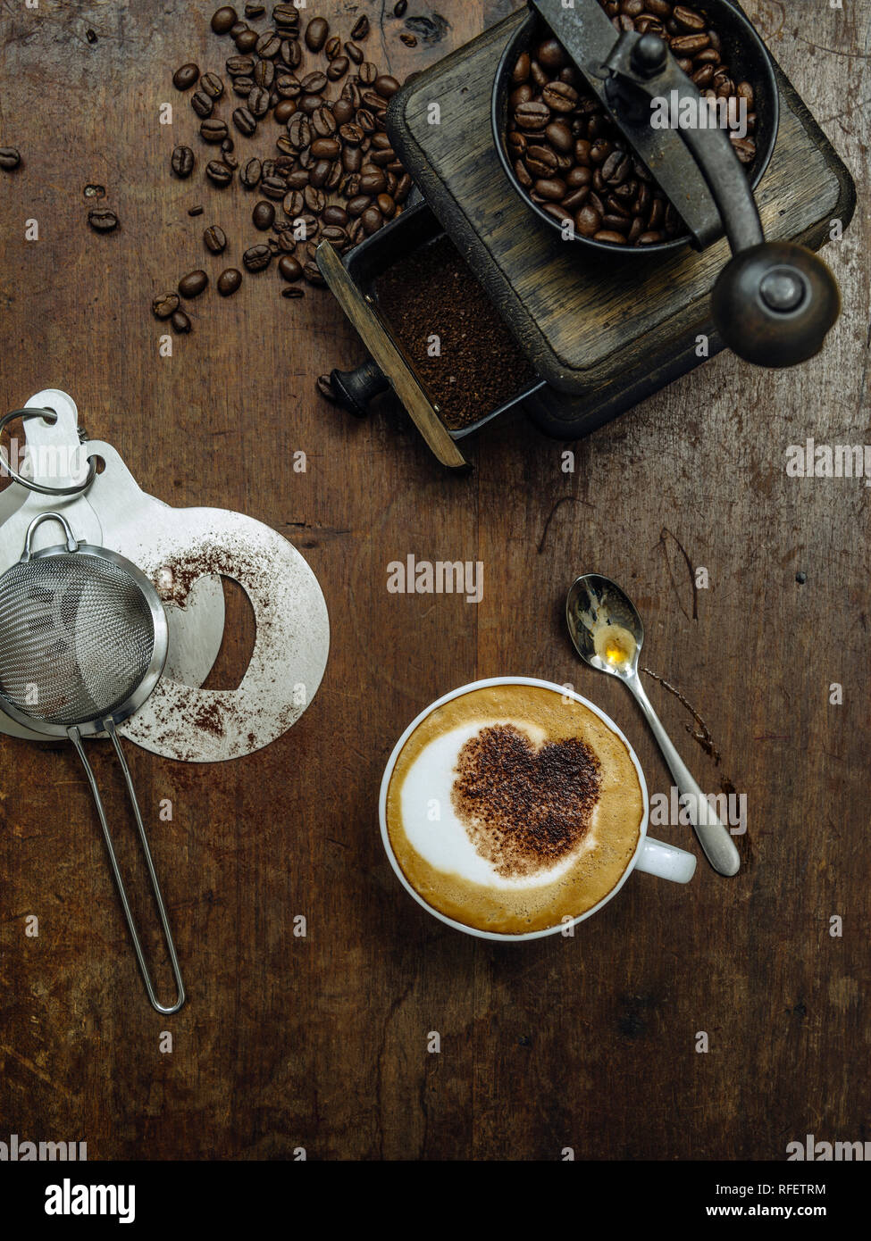 Photo of a messy rustic wooden table of coffee beans, grinder and a cup of coffee with heart-shaped chocolate sprinkle. - Stock Image