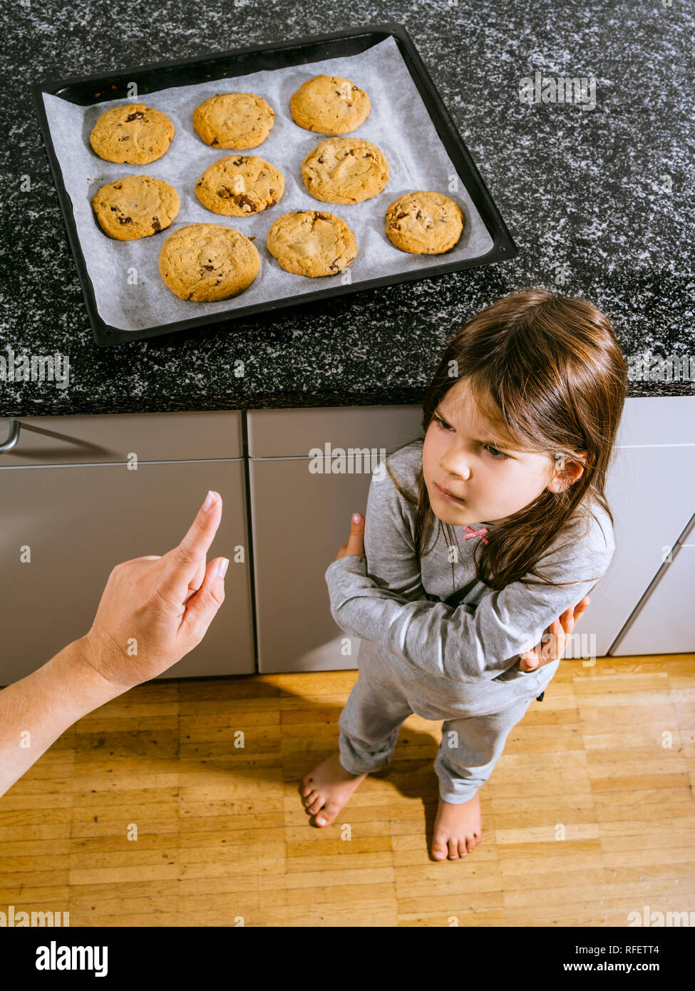 Photo of a young girl angry because her mother is telling her she cannot have any chocolate chip cookies from the baking tray. - Stock Image