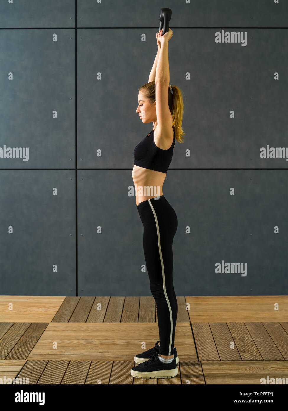 Photo of a young blond woman in her twenties exercising her shoulders with a kettlebell above her head. - Stock Image