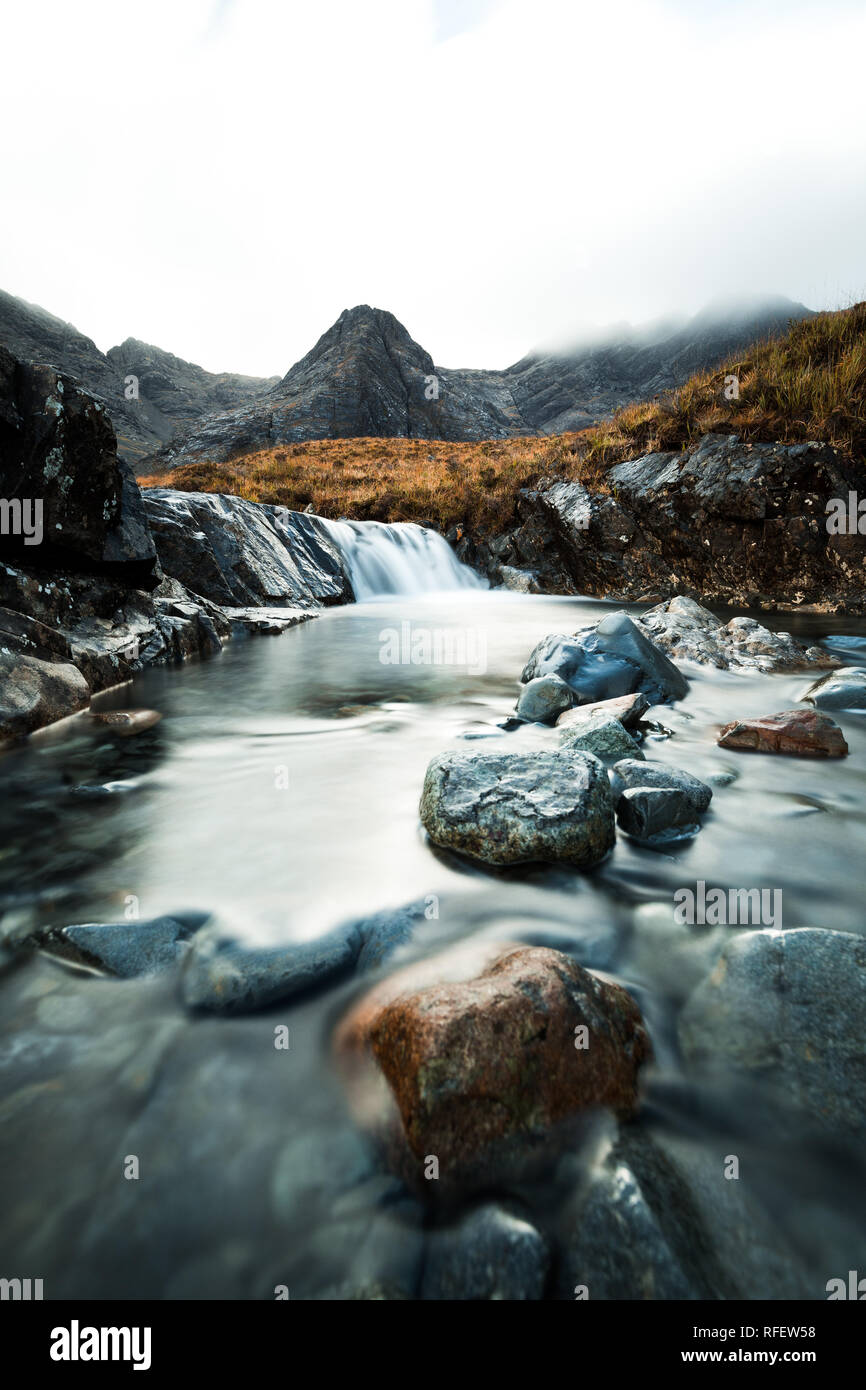 Picturesque waterfall with clear water and colourful stones in front of fog covered mountain range at the Fairy Pools (Isle of Skye, Scotland, Europe) - Stock Image