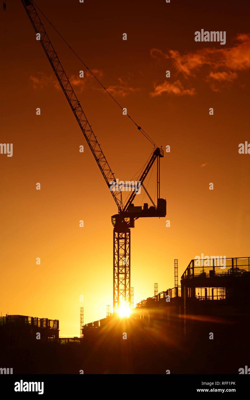 crane on building site at sunset on leeds city skyline yorkshire united kingdom - Stock Image