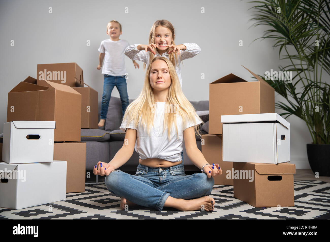 Photo of calm woman sitting on floor among cardboard boxes and boy, girl jumping on sofa - Stock Image