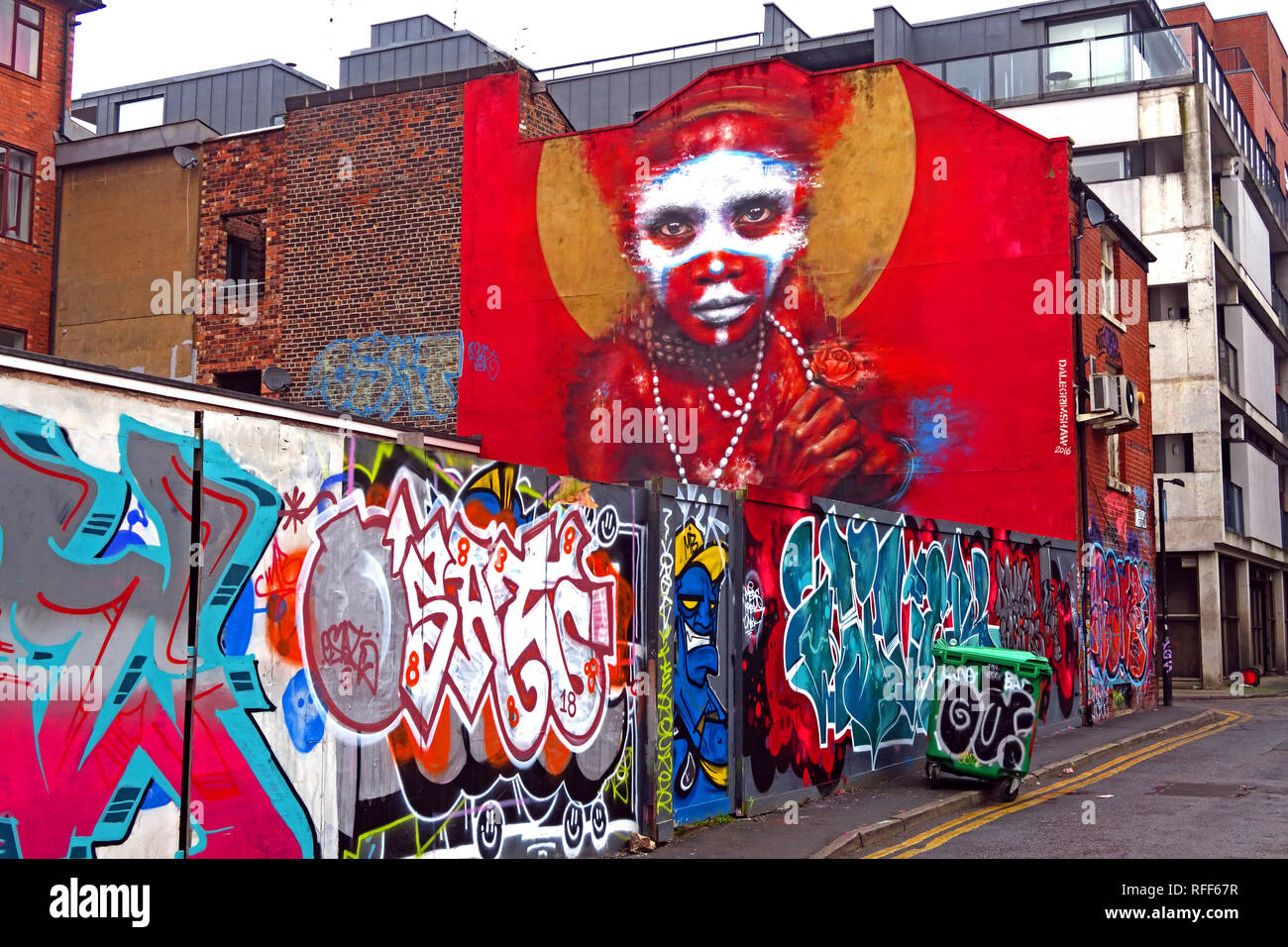 Aboriginal face on red background of graffiti, Spear St, Northern Quarter, Manchester, England, UK Stock Photo