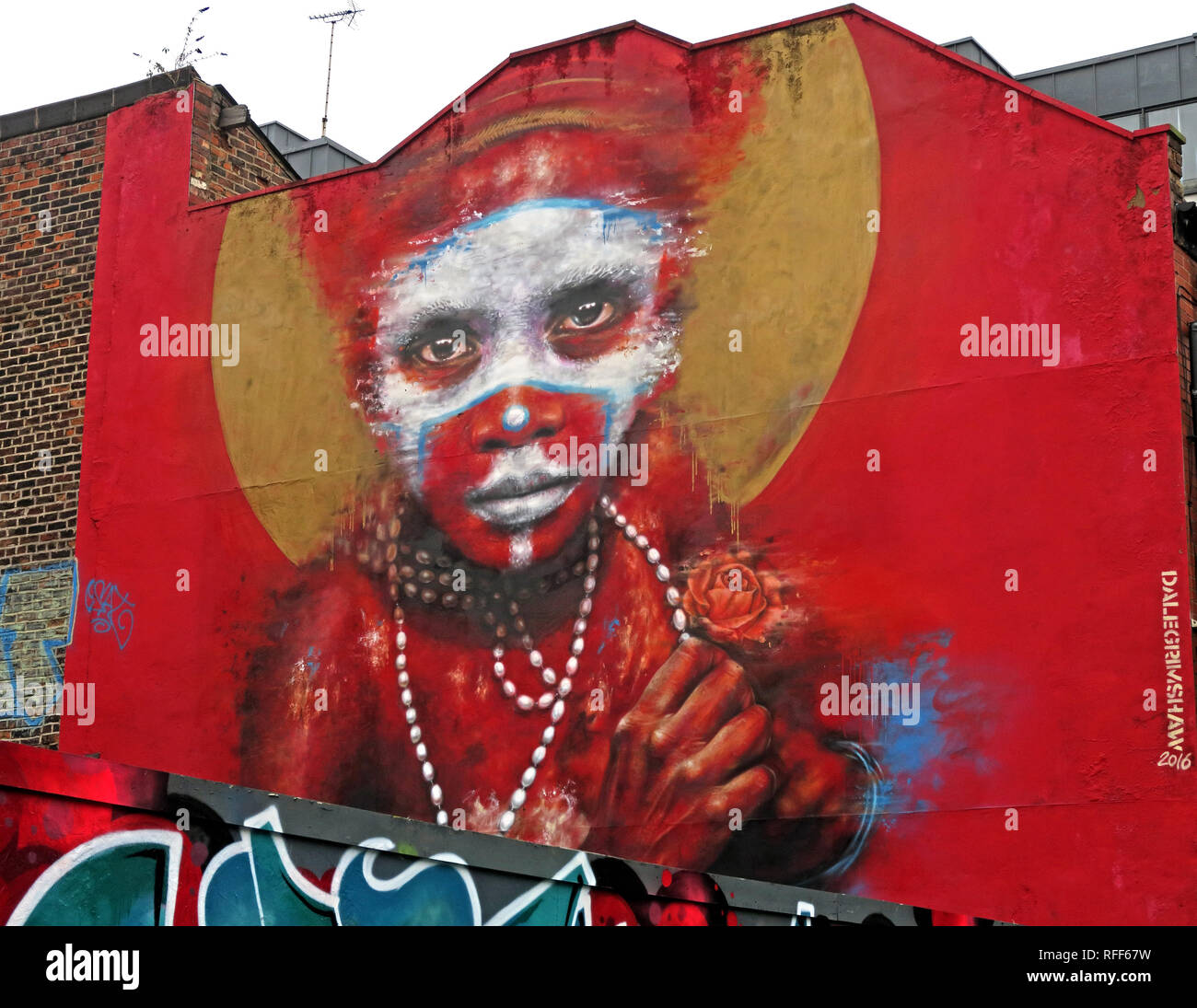 Aboriginal face on red background of graffiti, Spear St, Northern Quarter, Manchester, England, UK - Stock Image