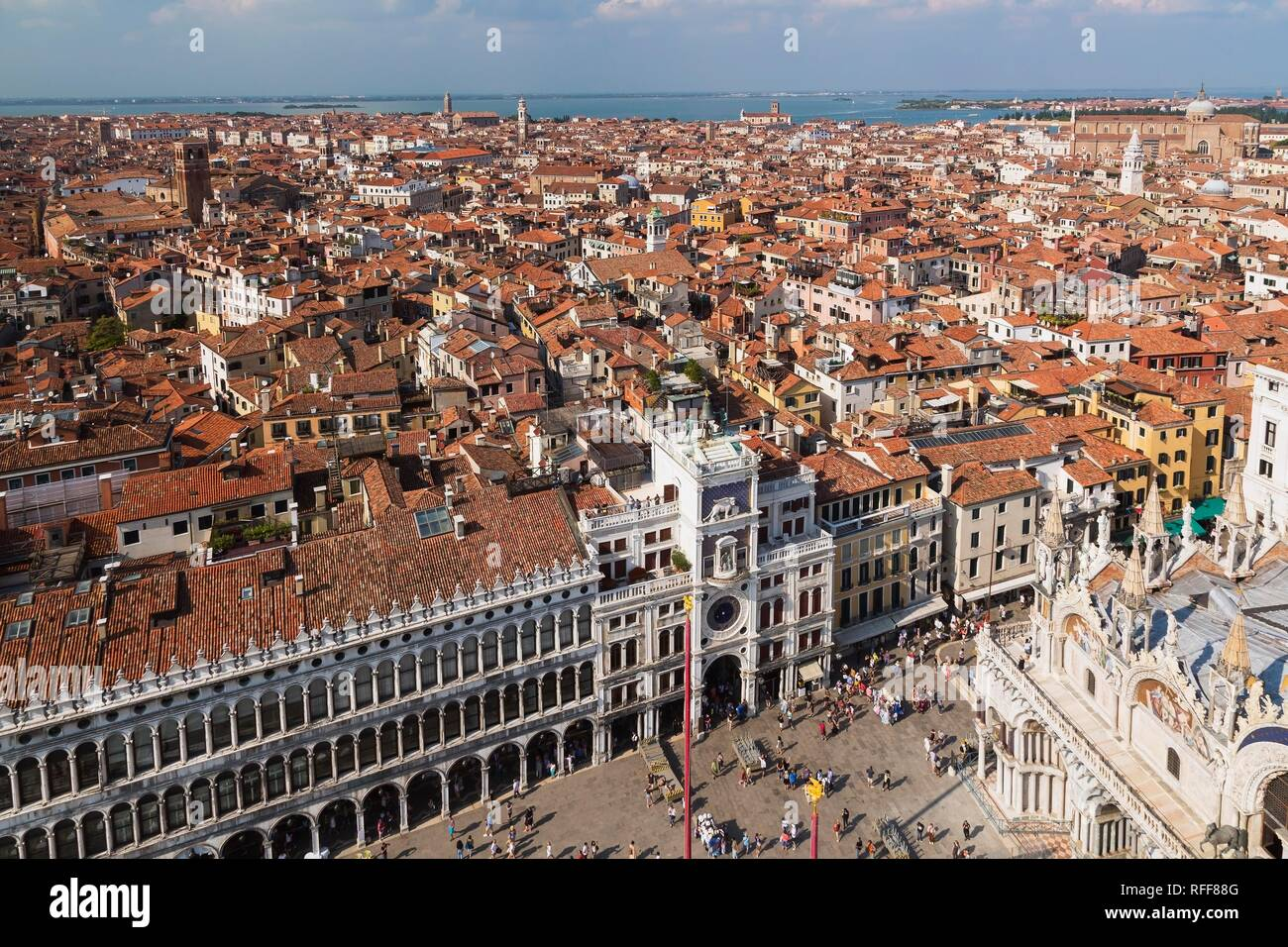 Procuratie Vecchie building with St Mark's clock tower and St Mark's Basilica and old architectural style residential buildings - Stock Image