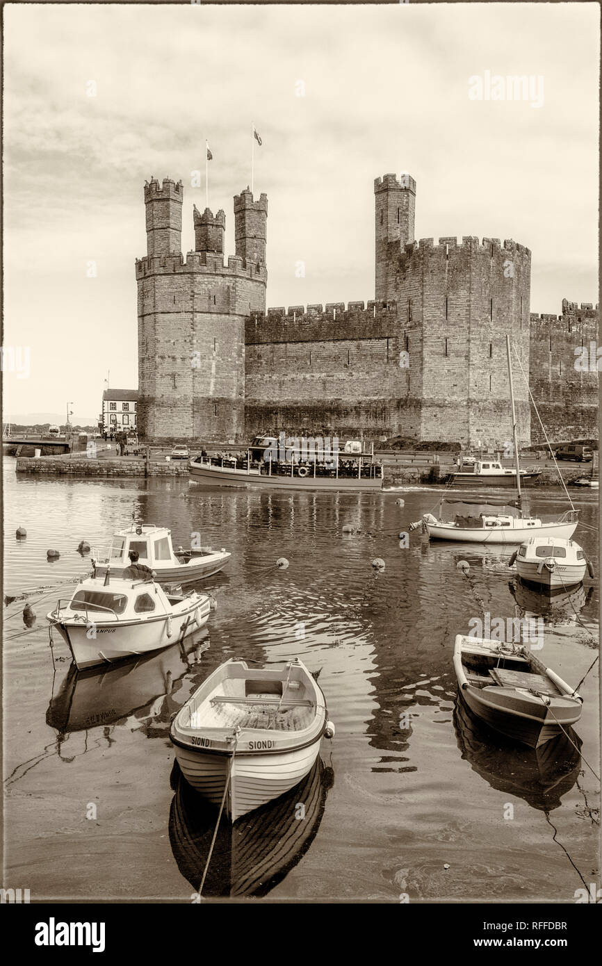 Caernarfon or Carnarvon or Caernarvon, Gwynedd, Wales, United Kingdom.  Caernarfon Castle seen across the River Seiont.  It is part of the UNESCO Worl - Stock Image