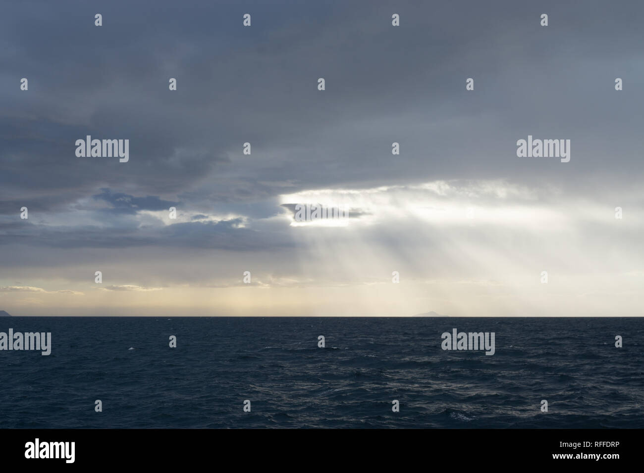 The god rays illuminated the sky over the Mediterranean Sea during my day cruise to Greek Island - Stock Image