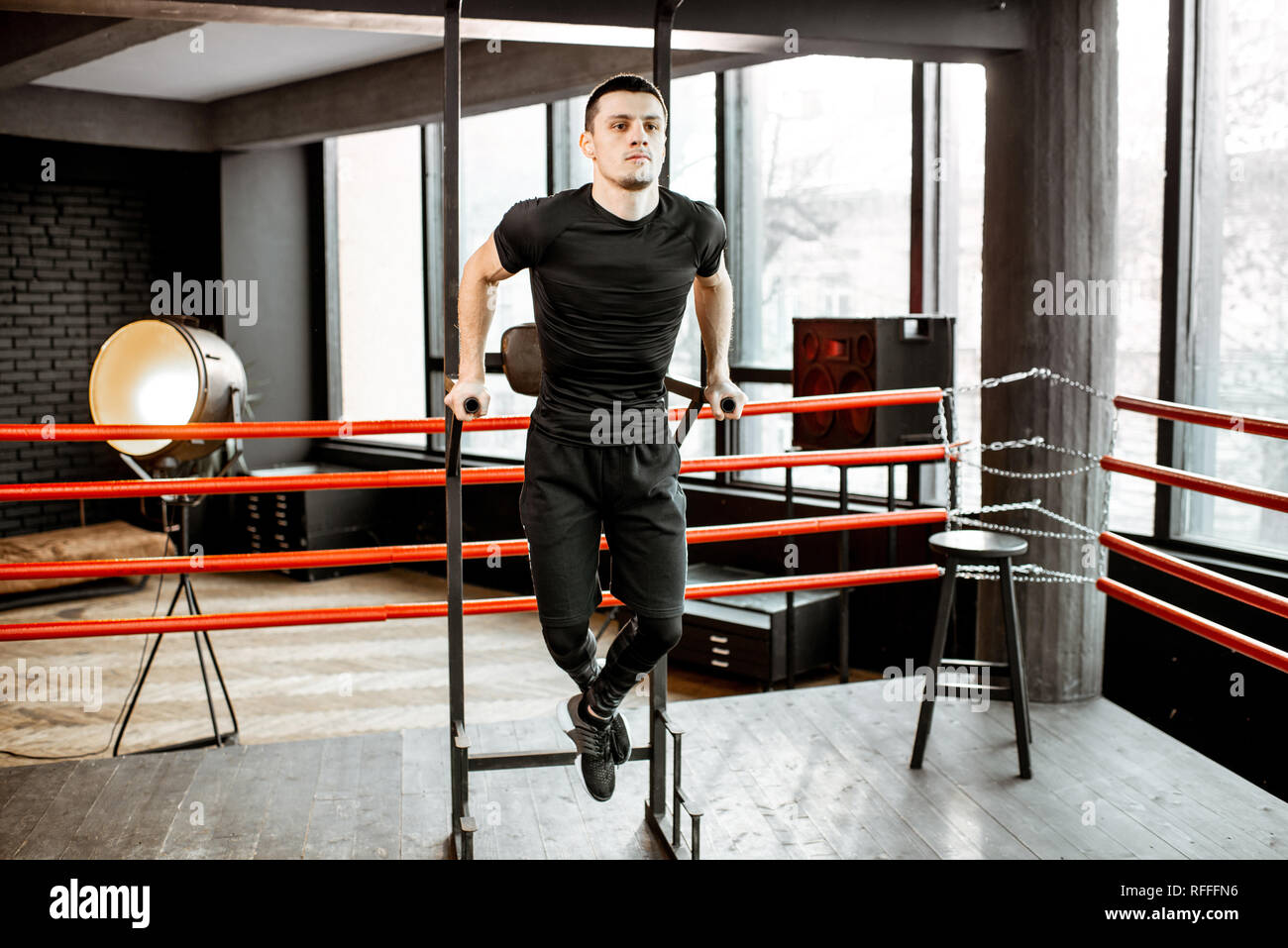 Young athletic man pulling up on the bar, warming up before the training on the boxing ring at the gym Stock Photo