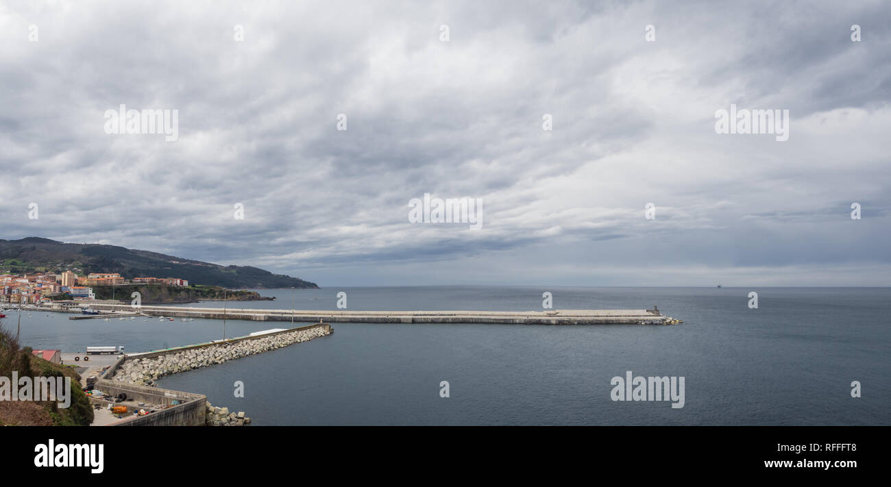 Breakwater of the fishing port of Bermeo on a cloudy day, Spain - Stock Image