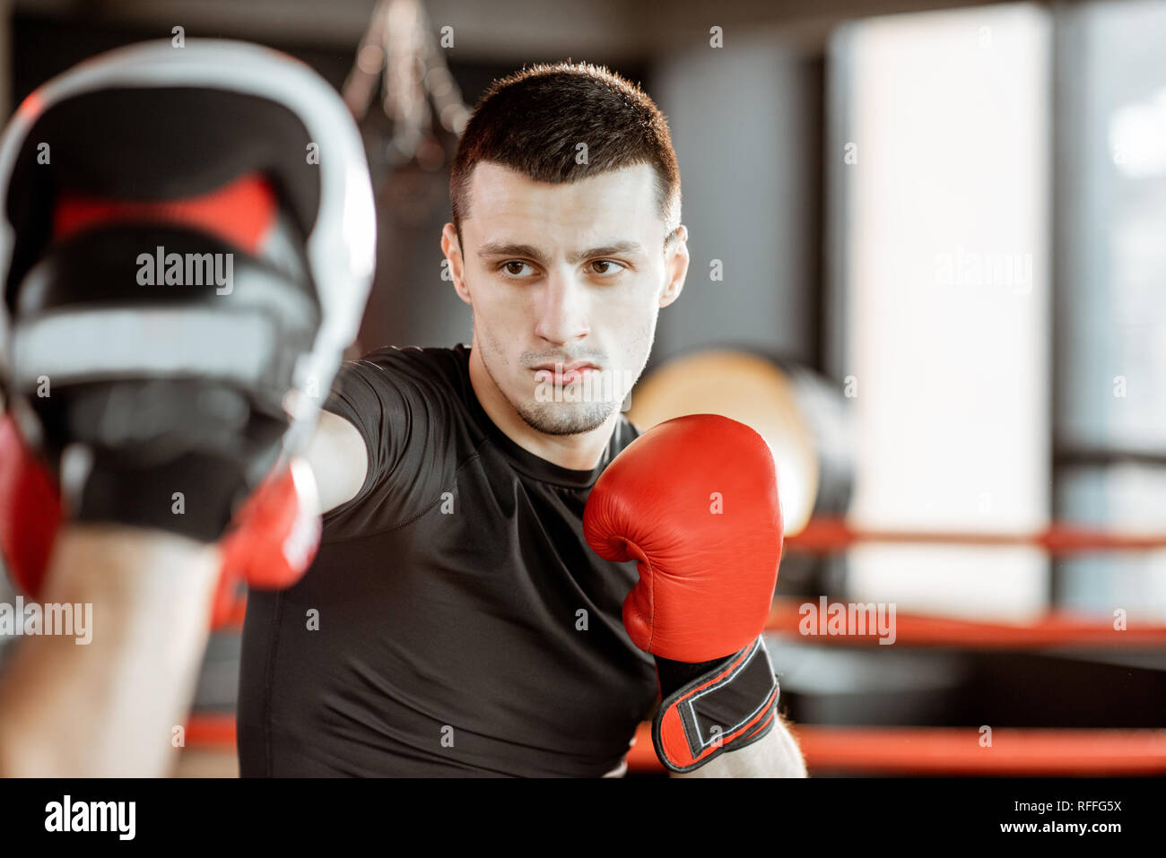 Athletic man fighting during the training with boxing trainer on the boxing ring at the gym - Stock Image