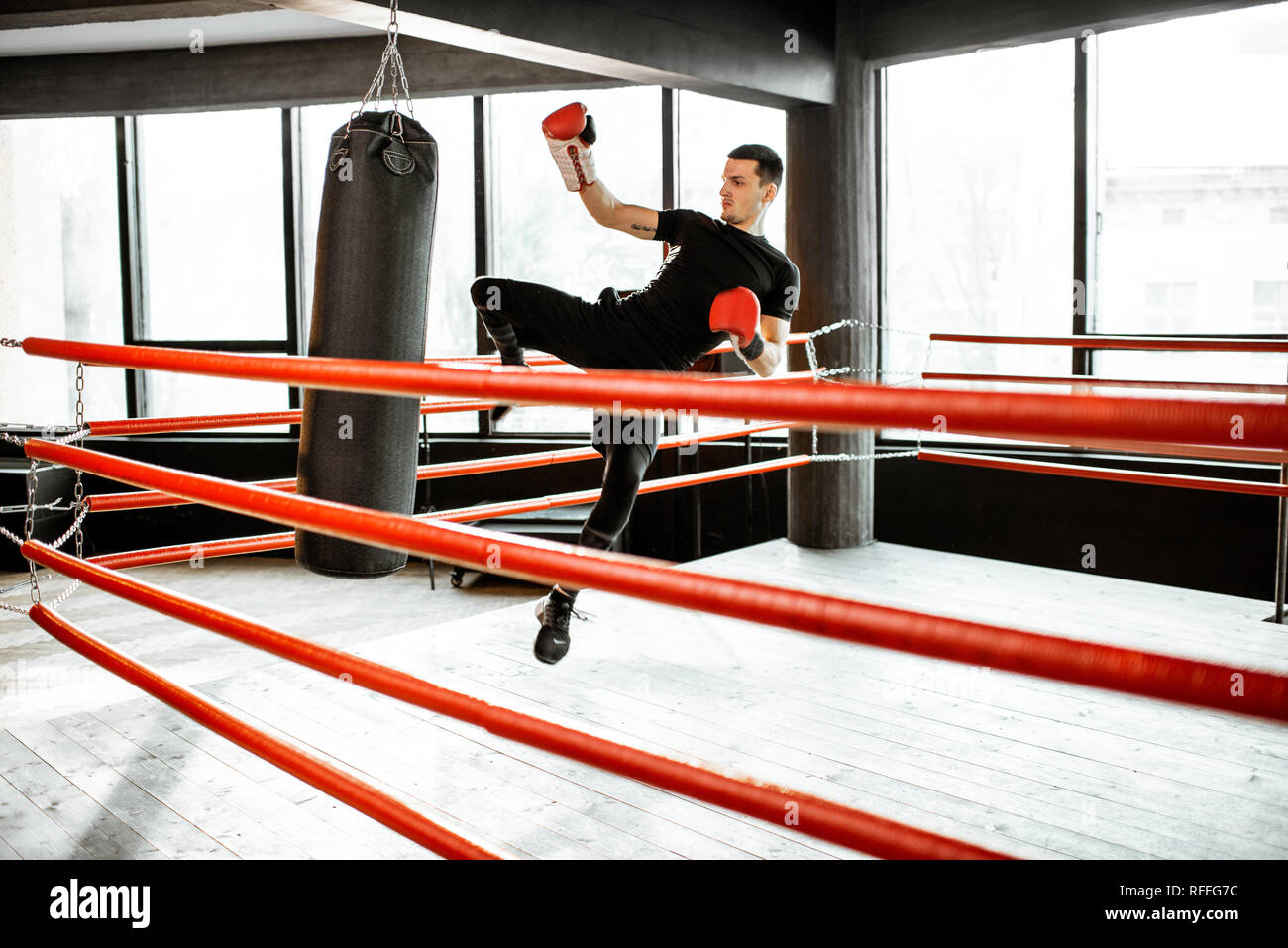 Athletic man kicking punching bag with leg, training kickboxing on the boxing ring at the gym - Stock Image