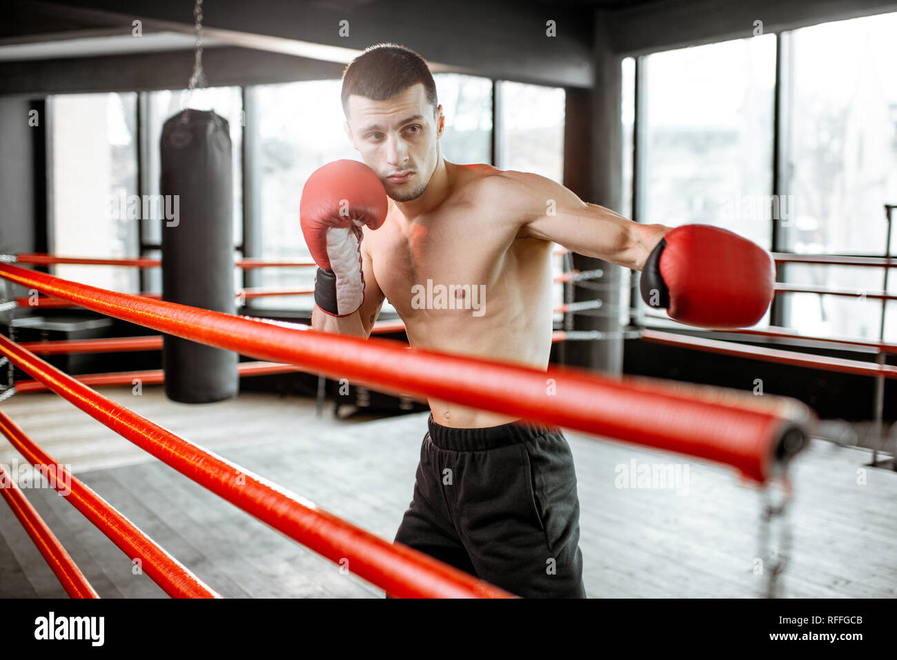 Young athletic man hard training to box, fighting on the boxing ring at the gym - Stock Image