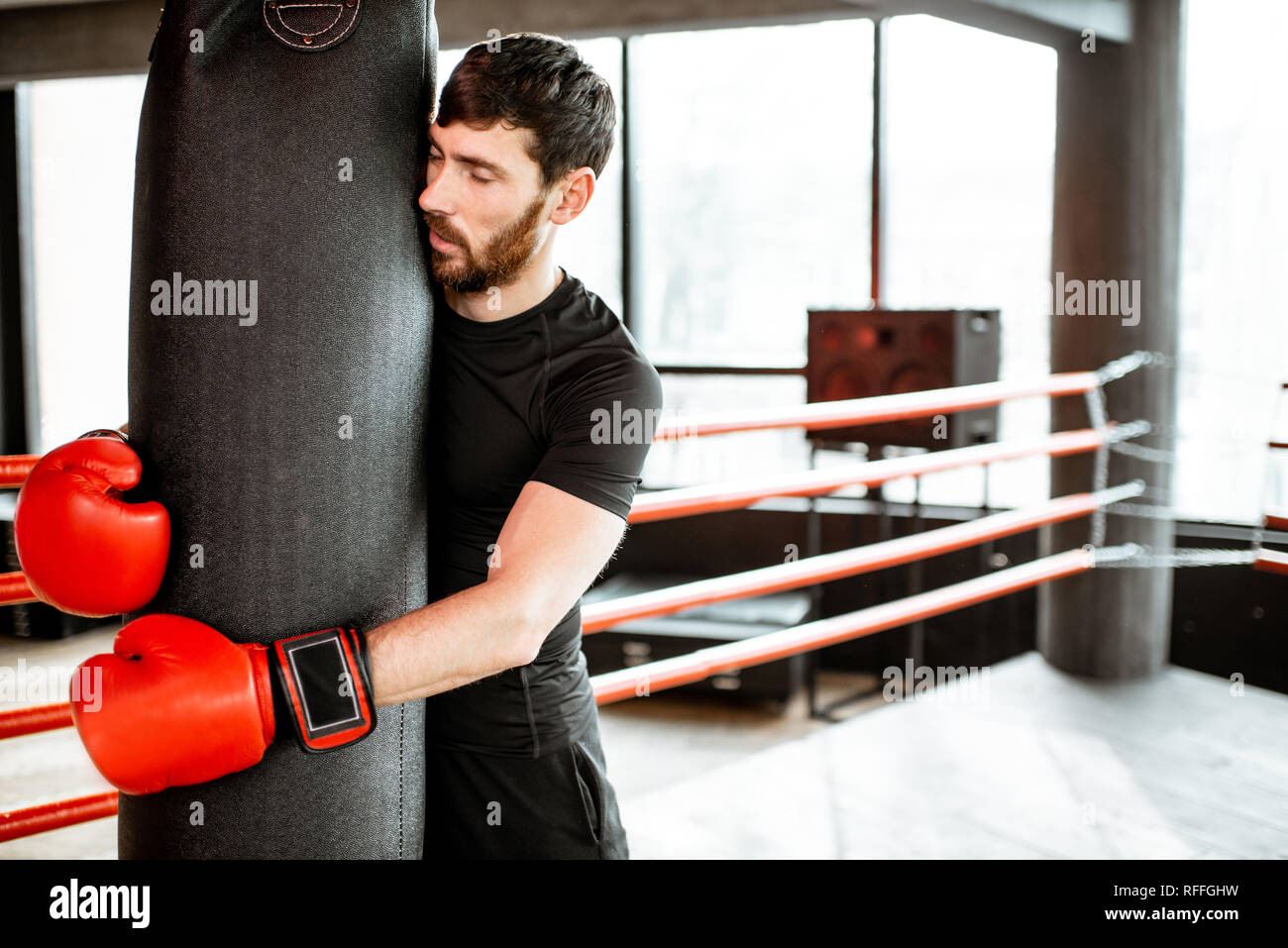 Exhausted man hugging punching bag after the training on the boxing ring at the gym - Stock Image