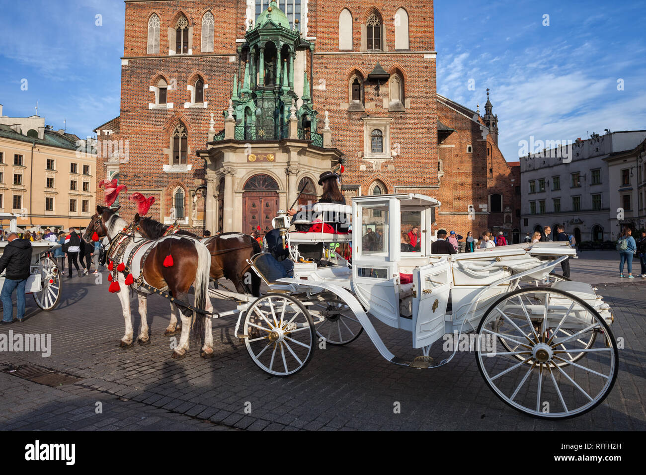 Poland, city of Krakow, horse carriage ride, sightseeing tour around the Old Town Main Market Square, Cloth Hall and St Adalbert Church in the backgro Stock Photo