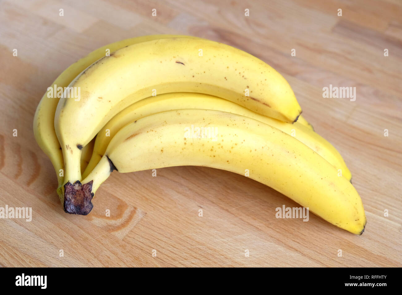 Ripe bananas lies on brown wooden table horizontal view real photo closeup - Stock Image