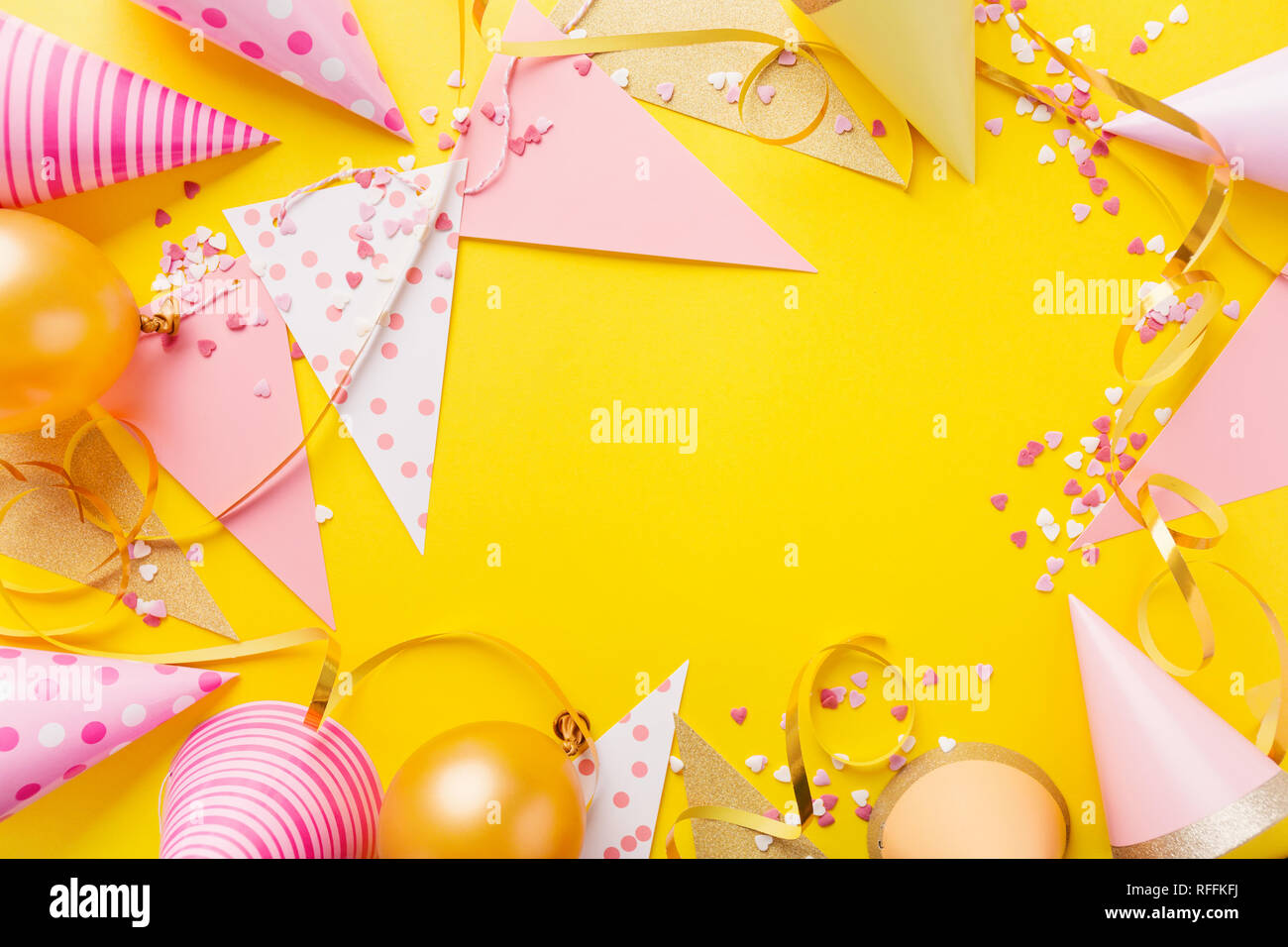 Colorful Happy Birthday Or Party Background Flat Lay Wtih Hats Confetti And Ribbons On Yellow Top View Wit Copy Space