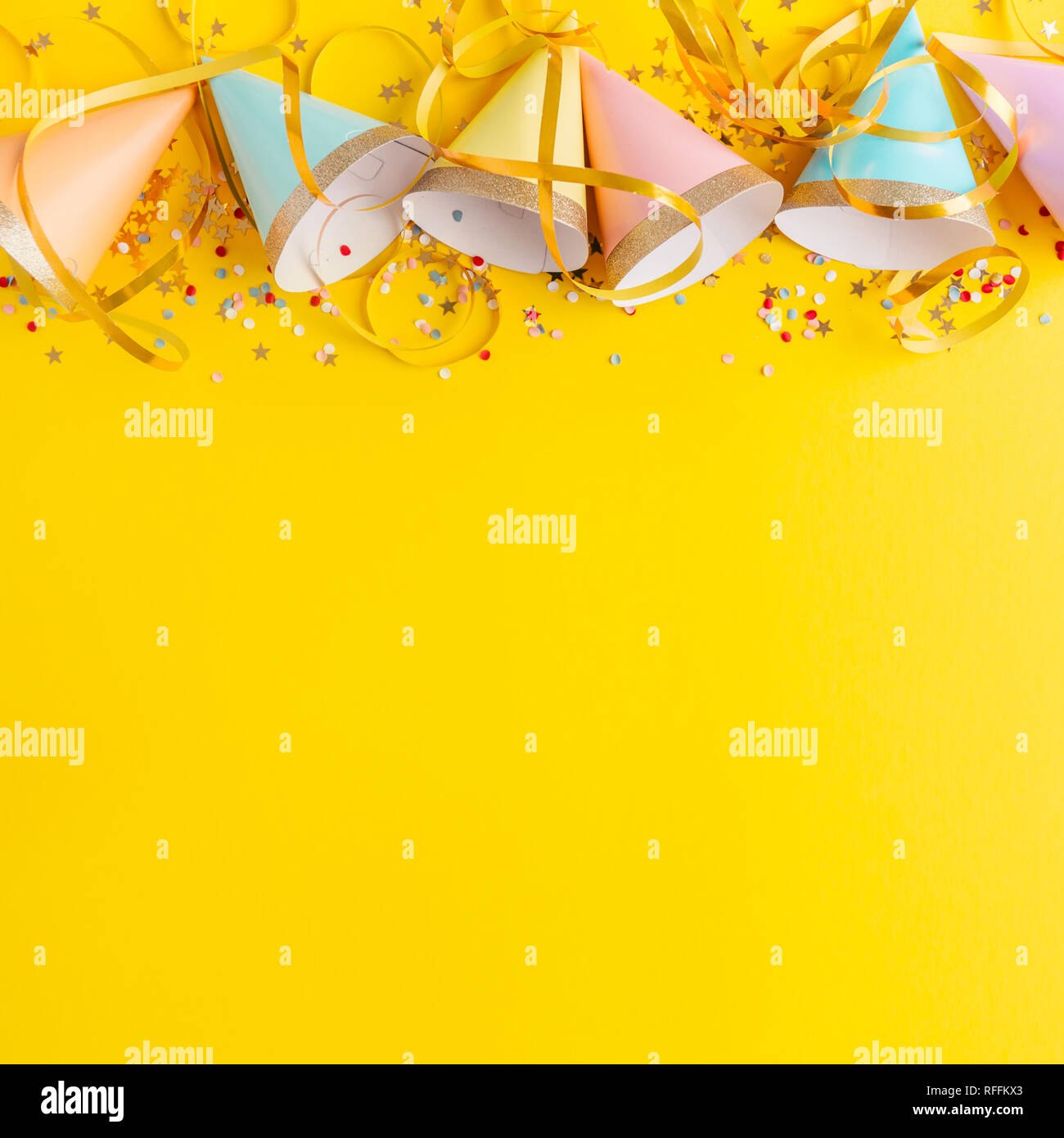 Colorful Happy Birthday Or Party Background Flat Lay Wtih Hats Confetti And Ribbons On Yellow Square