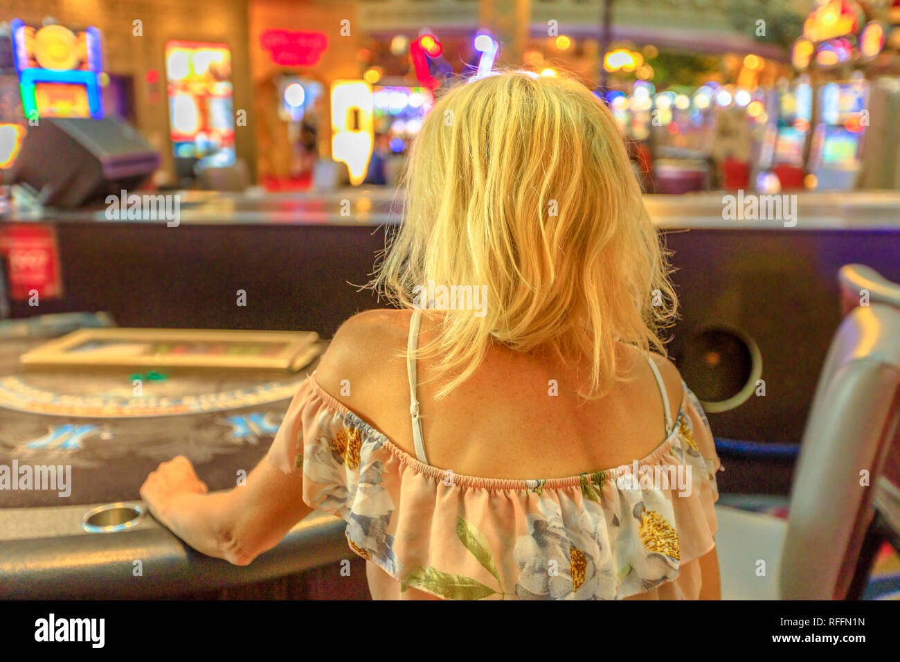 Caucasian blonde woman gambling in casino sitting at blackjack table. Gambler addict concept. Lifestyle girl play in casino at Las Vegas, Nevada - Stock Image