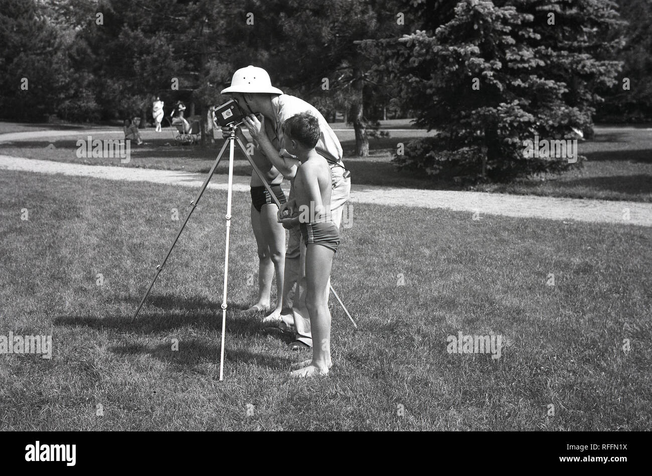1950s, historical, two young boys in swimming costumes stand by a man with a tripod filming with a home movie film or cine-camera in a park. In this era. filming or recording family moments with a small portable cine camera was a popular hobby and there were many different formats and cameras available. - Stock Image