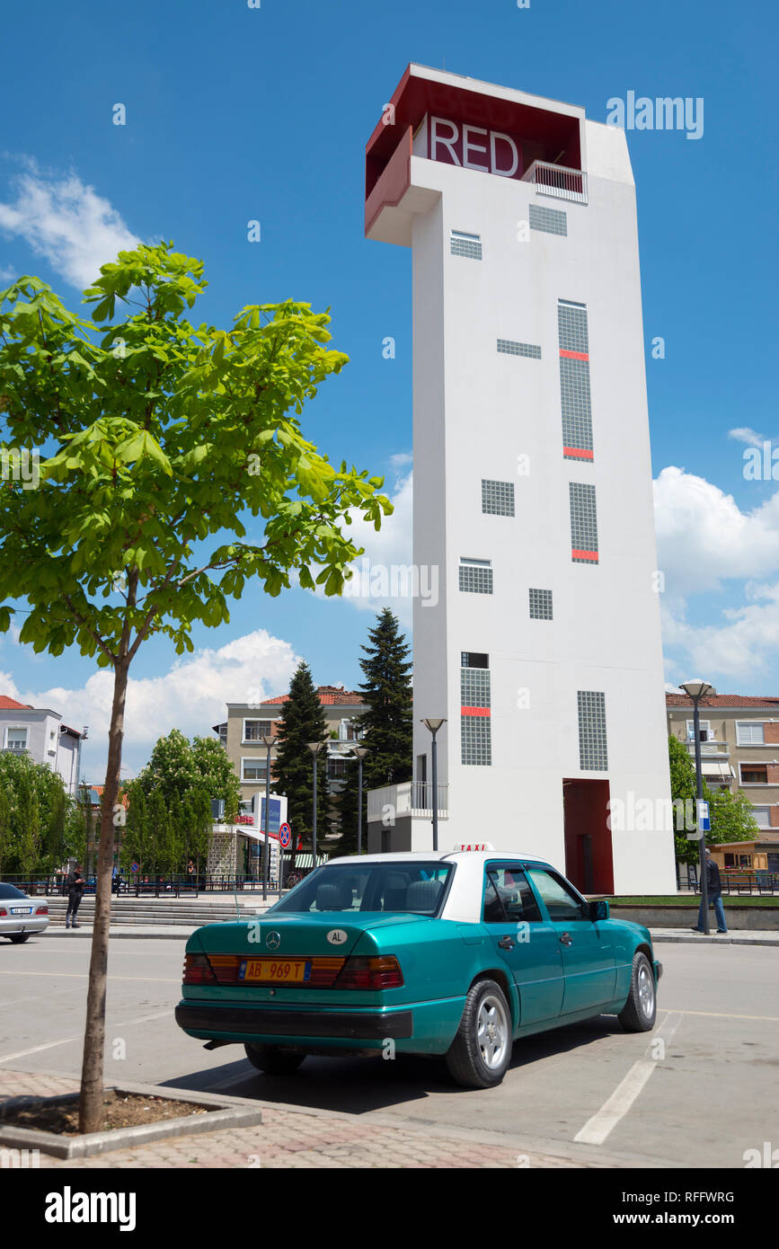 Mercedes taxi in front of observation tower Red Tower on theater square, Korca, Albania, Korça - Stock Image