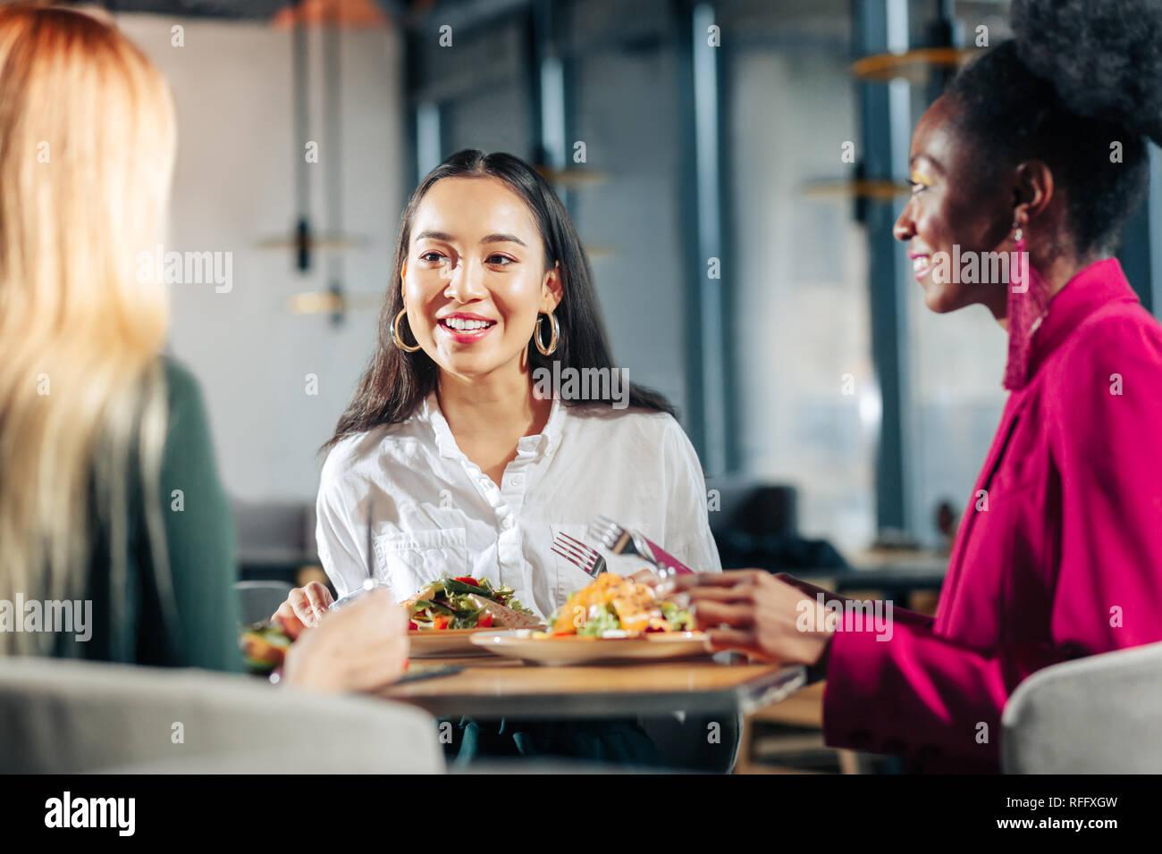 Three young businesswomen having informal meeting in restaurant - Stock Image