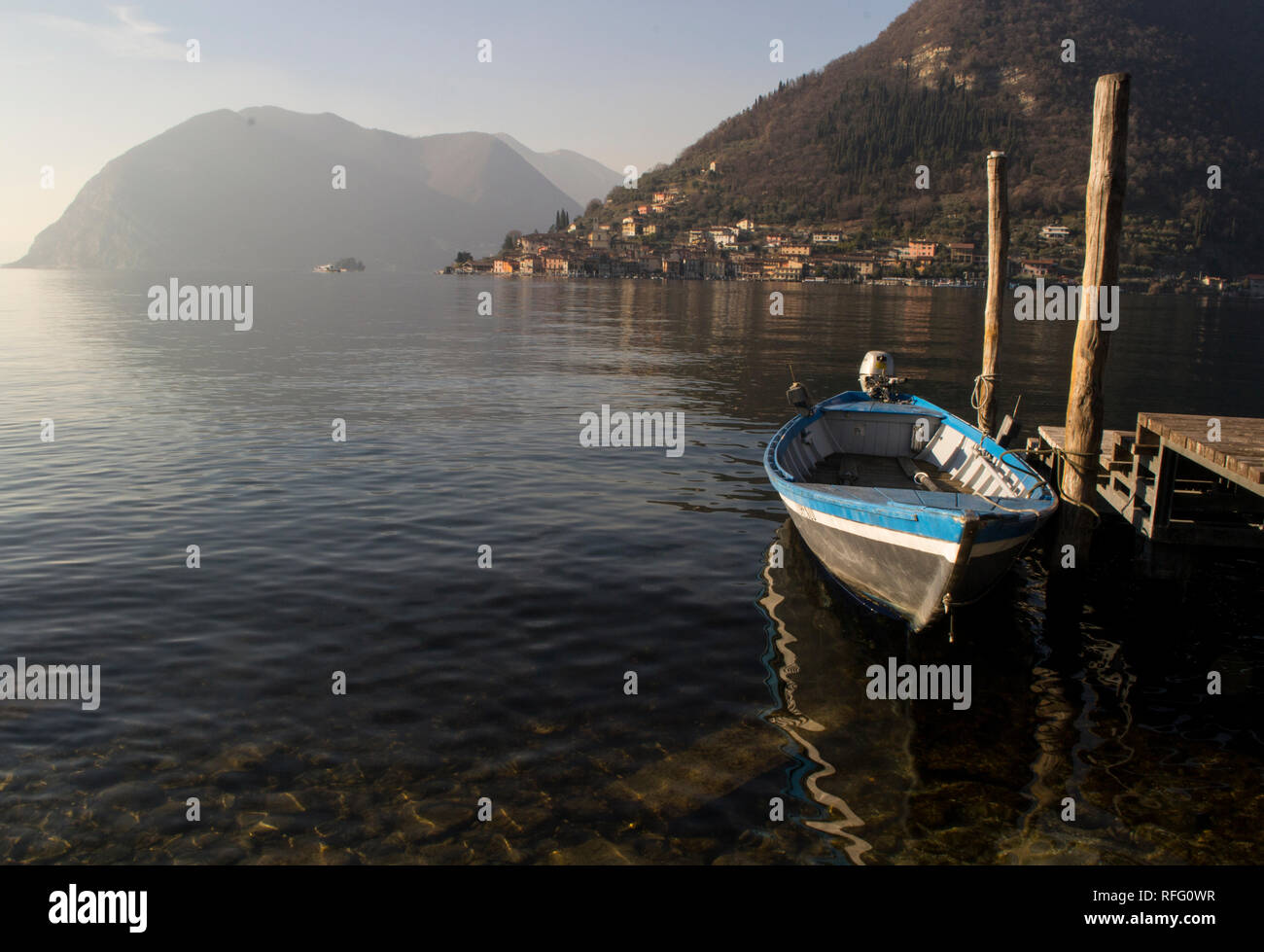 Little boat parked near a wooden pier on Iseo lake in Northern Italy, view on Monte Isola island. - Stock Image