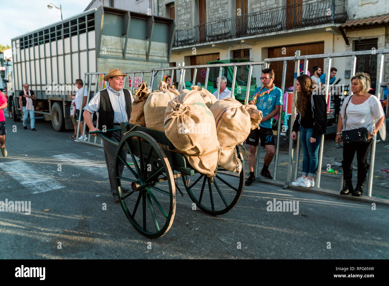 Frenchman pushing sacks of goods, Old School Parade of traditional trades at Annual Fete, Saint Gilles, Gard, France - Stock Image