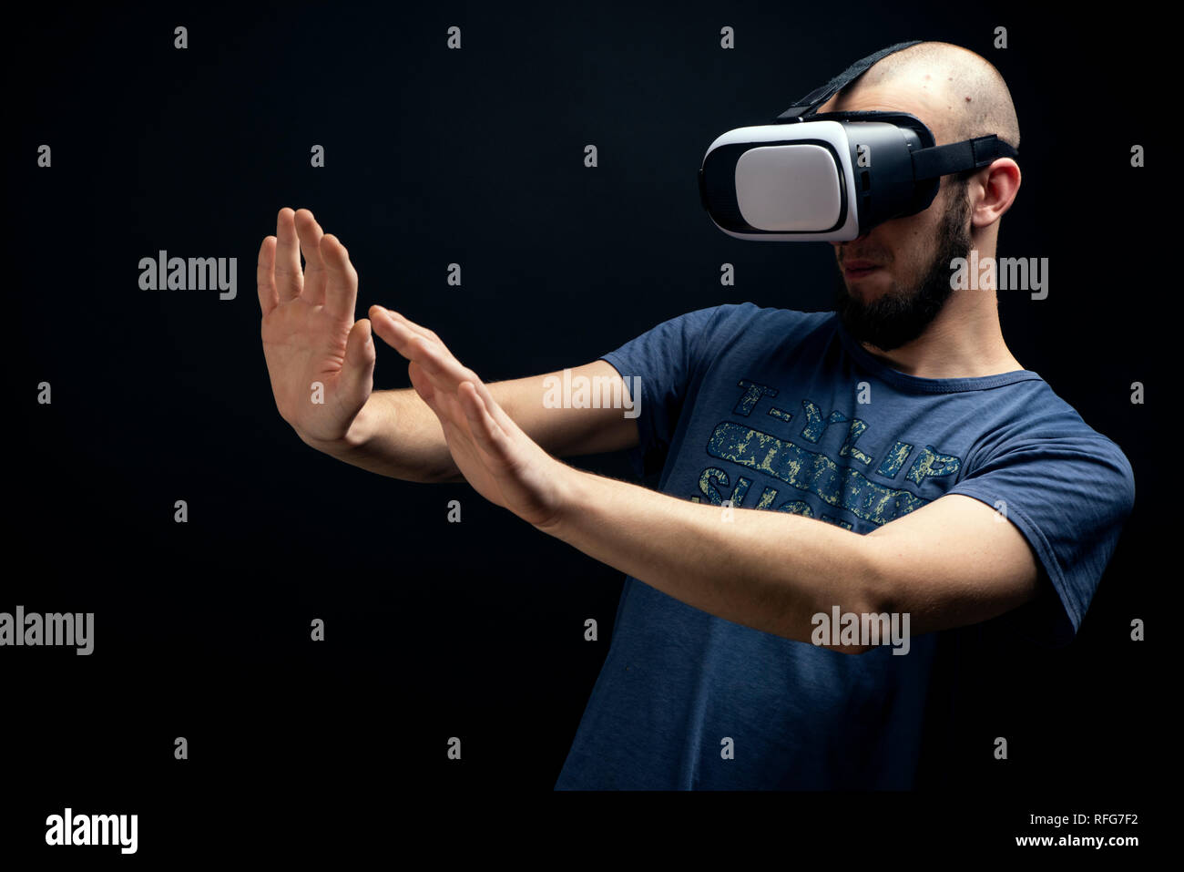 Male using VR gear is dodging with both hands. Shot in studio against black background - Stock Image