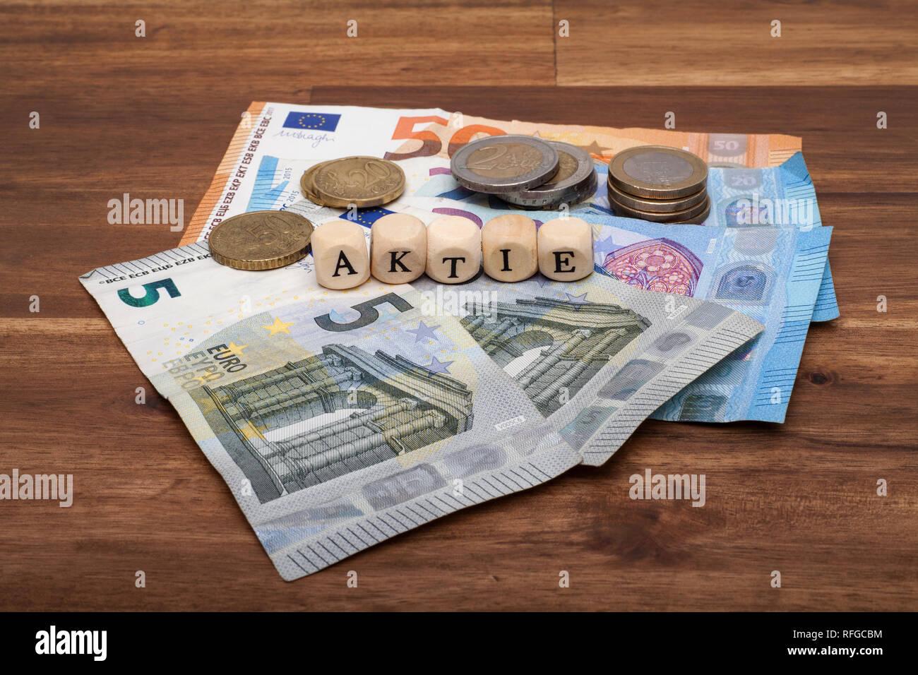 Die Euro Geldscheine und Münzen liegen auf dem Tisch mit dem Wort Aktie - Stock Image