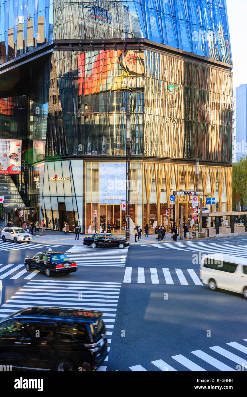 The Tokyo Ginza. Daytime, cars driving over the scramble zabra crossing at the corner of the illuminated Tokyu Plaza building with the Bally store. - Stock Image
