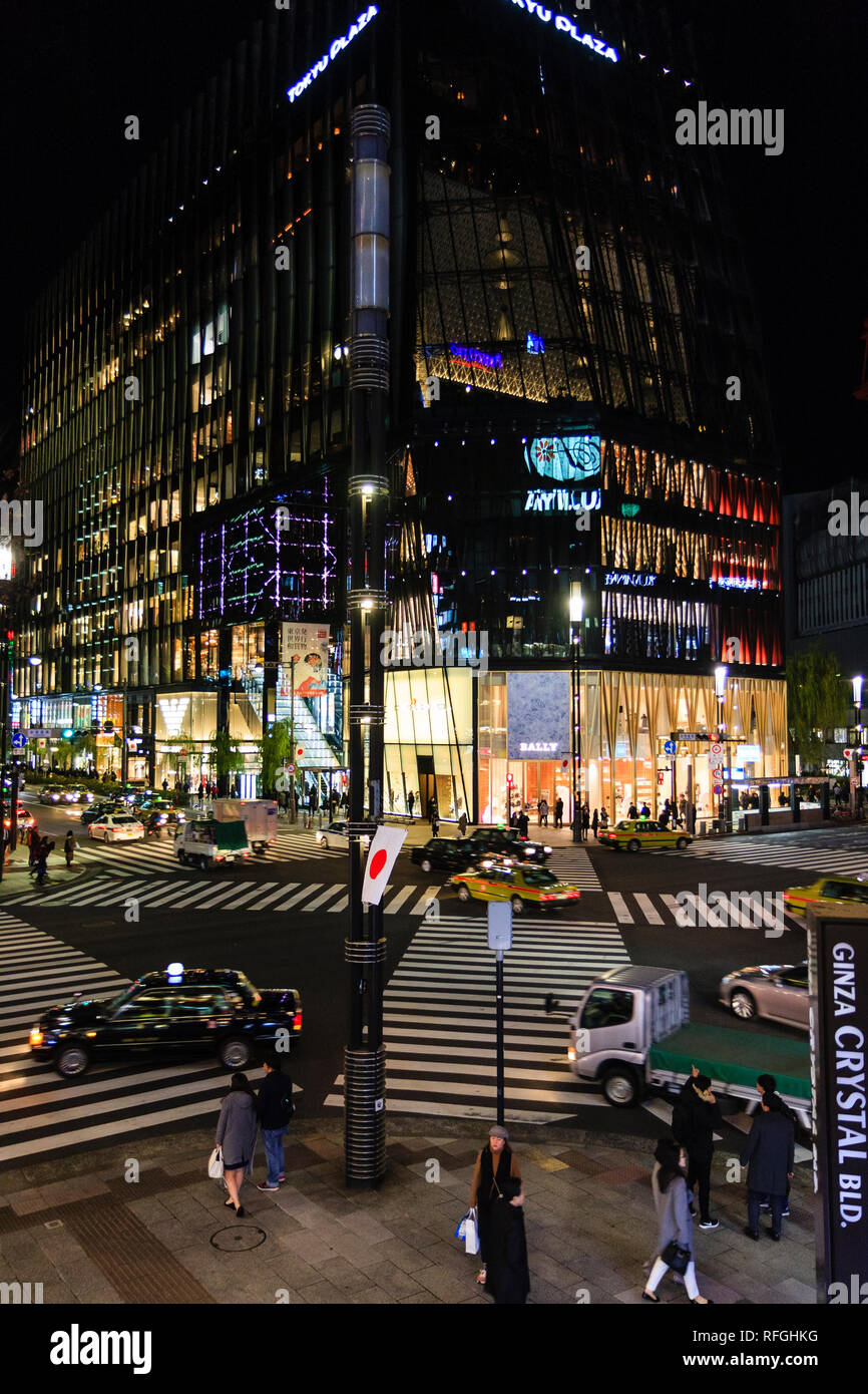 The Tokyo Ginza at night time, cars driving over the scramble zabra crossing at the corner of the illuminated Tokyu Plaza building with the Bally stor - Stock Image