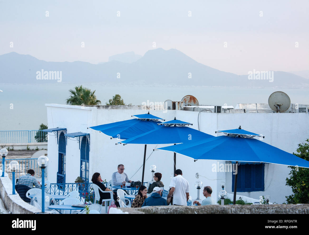 People at cafe. Behind sea and mountains - Stock Image