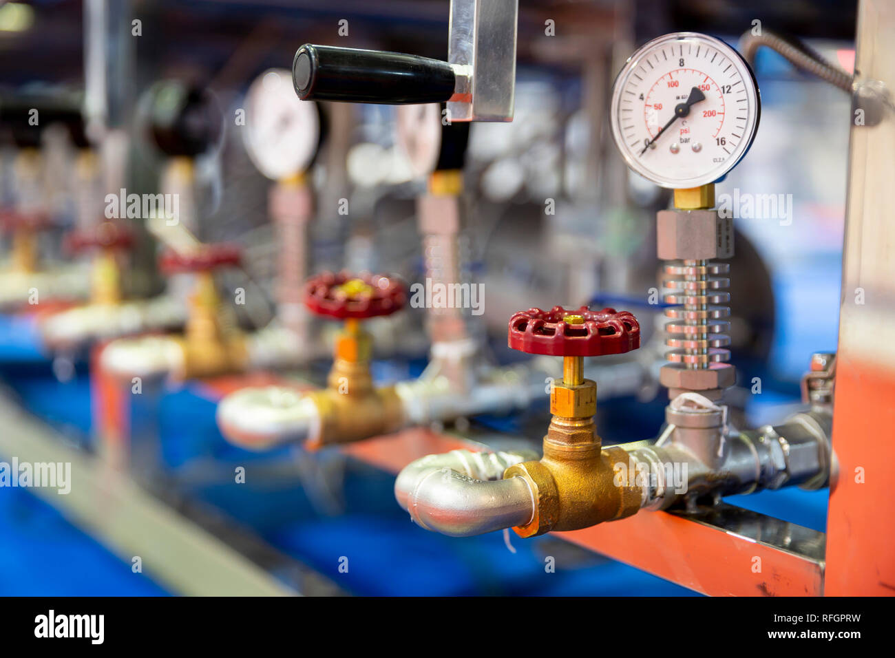 Pressure measuring instrument - bar, psi. Red metal valves on the pipes. Pressure device for industry system. - Stock Image