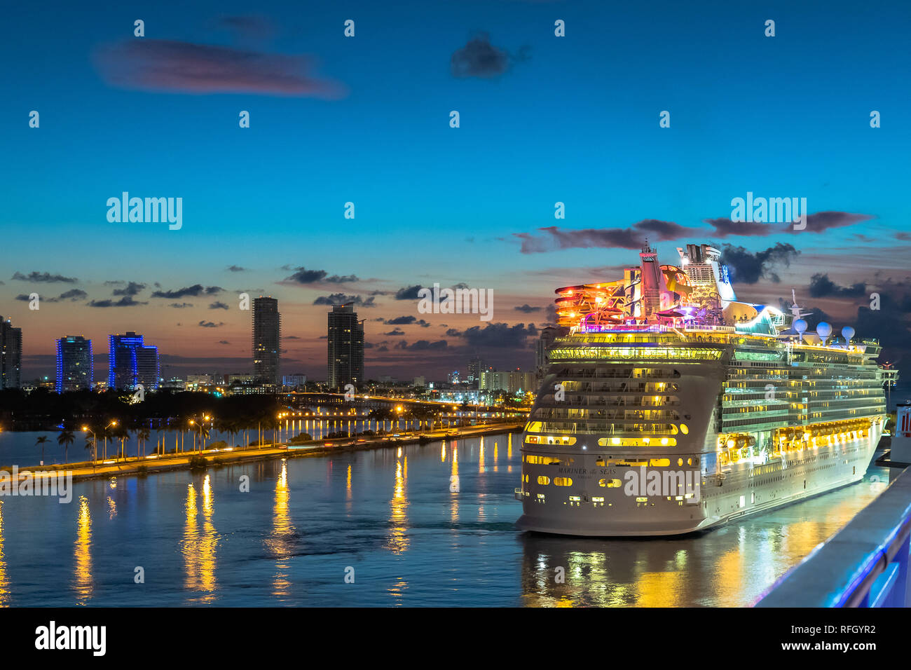 Miami, Florida - November 19 2018: Royal Caribbean Cruise Line Mariner Of The Seas Cruise Ship sailing in the Port of Miami at sunrise with skyline of - Stock Image