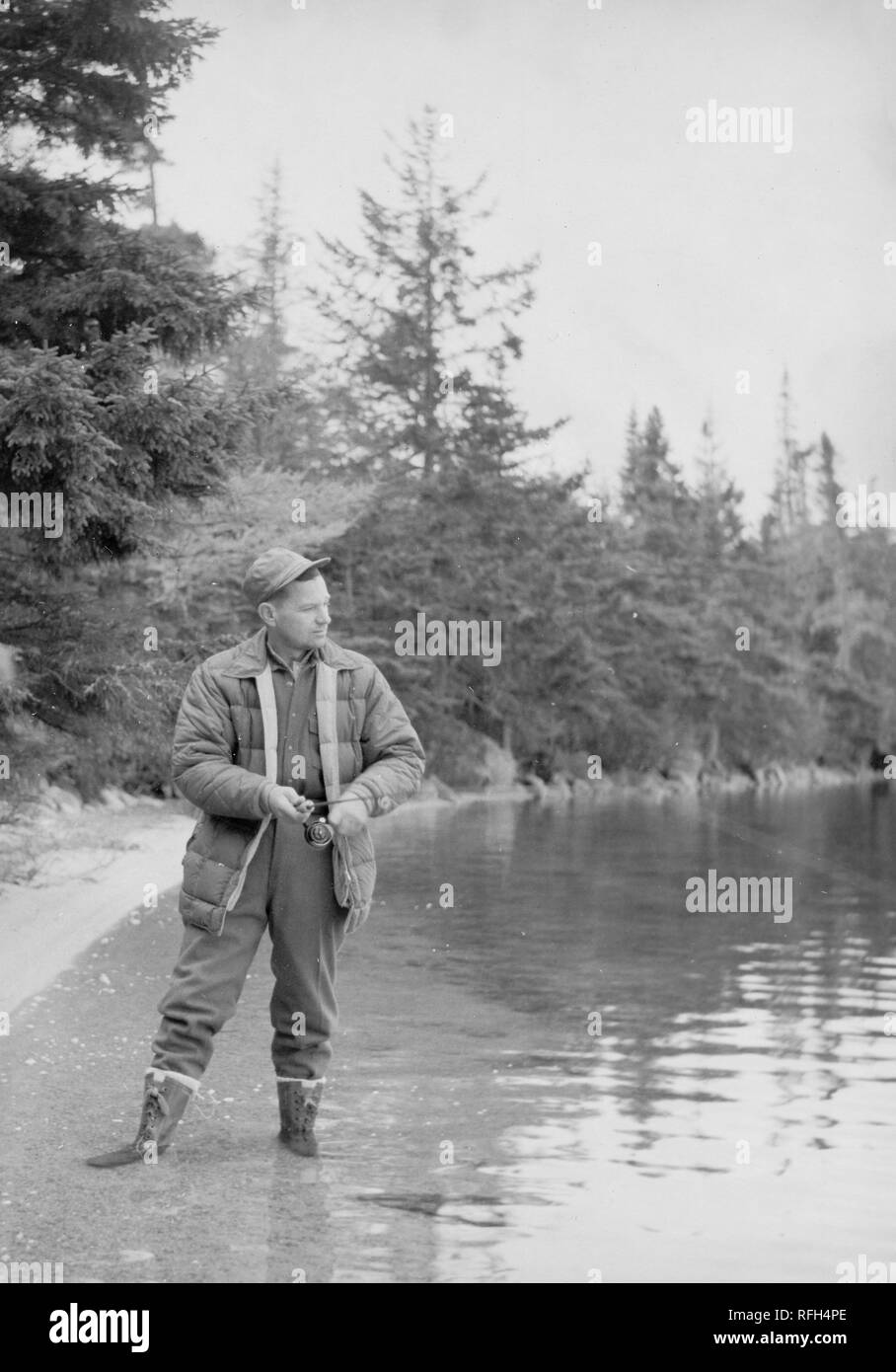 Black and white photograph of a middle-aged man, wearing a jacket, overalls, boots, and cap, shown in full-length view, standing in a body of water with his boots submerged to the ankle, with his head turned in profile to look toward the line of a fishing rod which he reels with both hands, with trees and foliage visible in the background, photographed during a hunting trip located in Alaska, USA, 1955. () - Stock Image