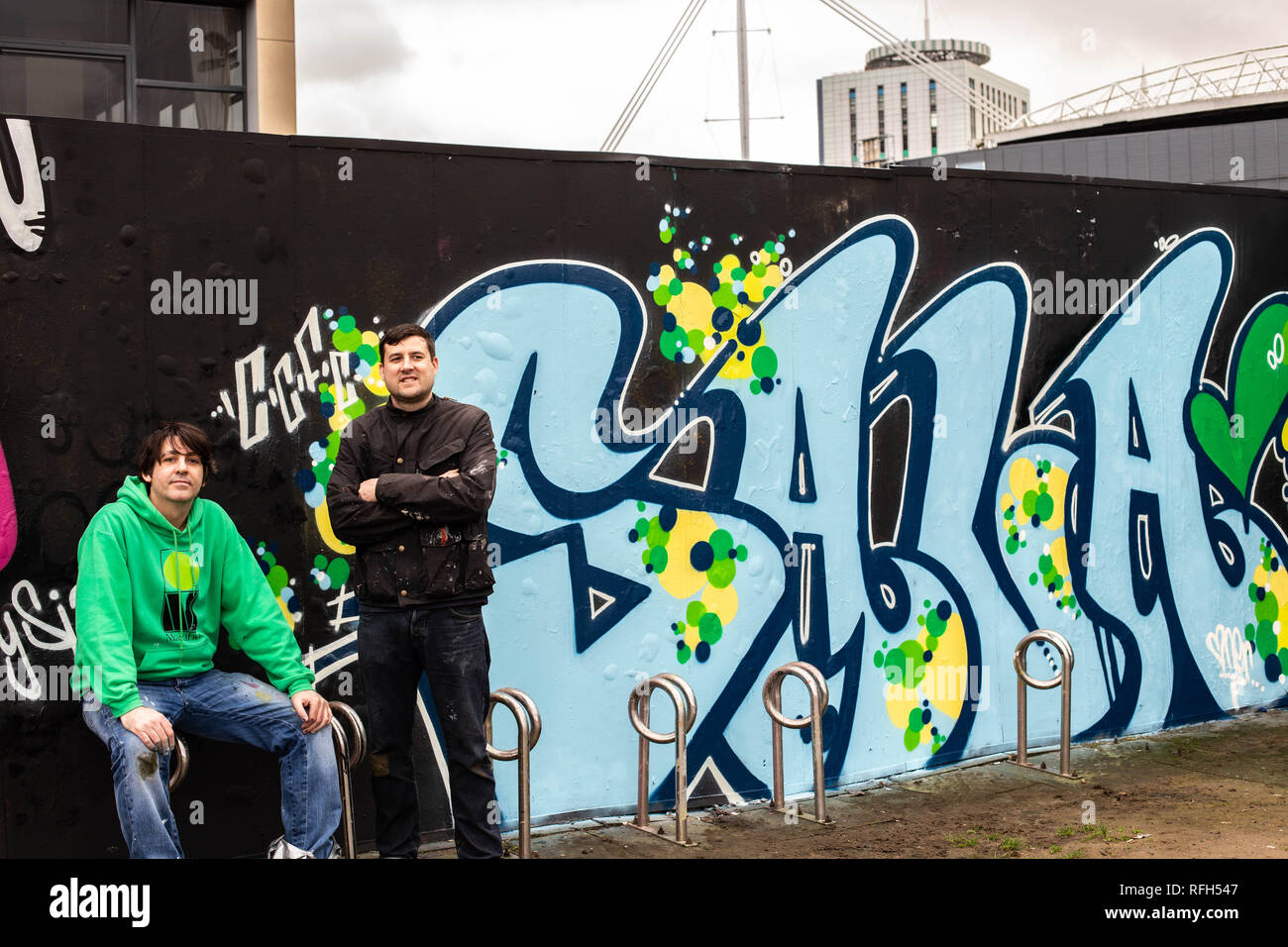 Cardiff, Wales, UK. 25th January 2019. Kieron and Scott of Church Street's Oner Signs, pose beside their graffiti artwork, which is a tribute to Emilano Sala - the football player who had just signed to Cardiff City Football Club but is now presumed dead after his flight from Nantes, France, had gone missing. © Amy Farrer Credit: Amy Farrer/Alamy Live News - Stock Image